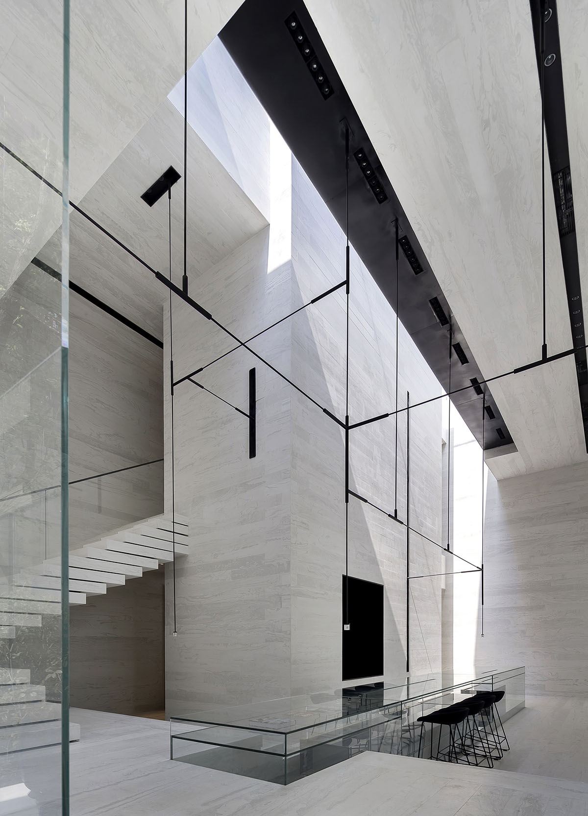 Luxury gym in china embraces sleek and minimal design curbed a black metal light fixture made of connected horizontal and vertical tubes hangs down from the ceiling dailygadgetfo Choice Image