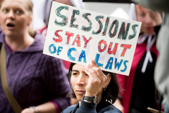 "People protest outside a speech by US Attorney General Jeff Sessions March 7, 2018, in Sacramento, California. Sessions and the Department of Justice are suing California over its ""sanctuary laws."""