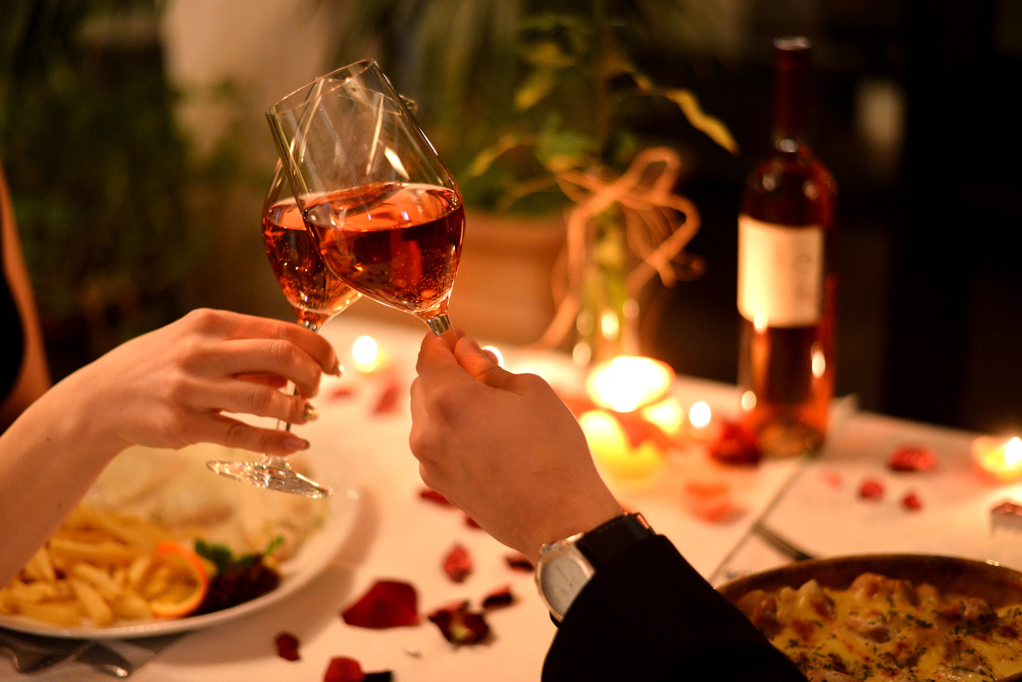 Two hands reach in from the sides of the photo, clinking champagne glasses over a candelit dinner table with rose petals scattered on it