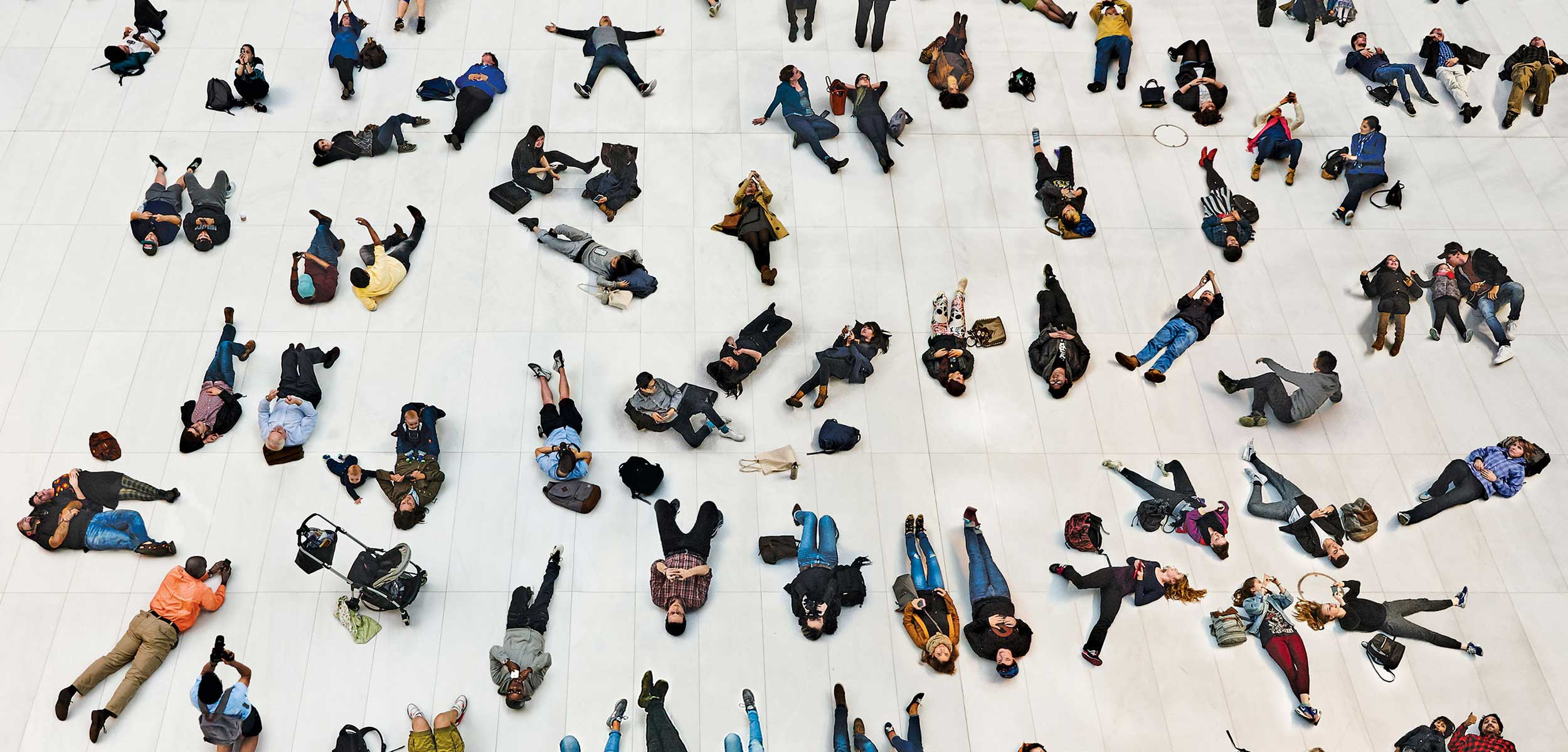 Commuters lying on ground in staged photo for opening of Oculus Transportation Hub.