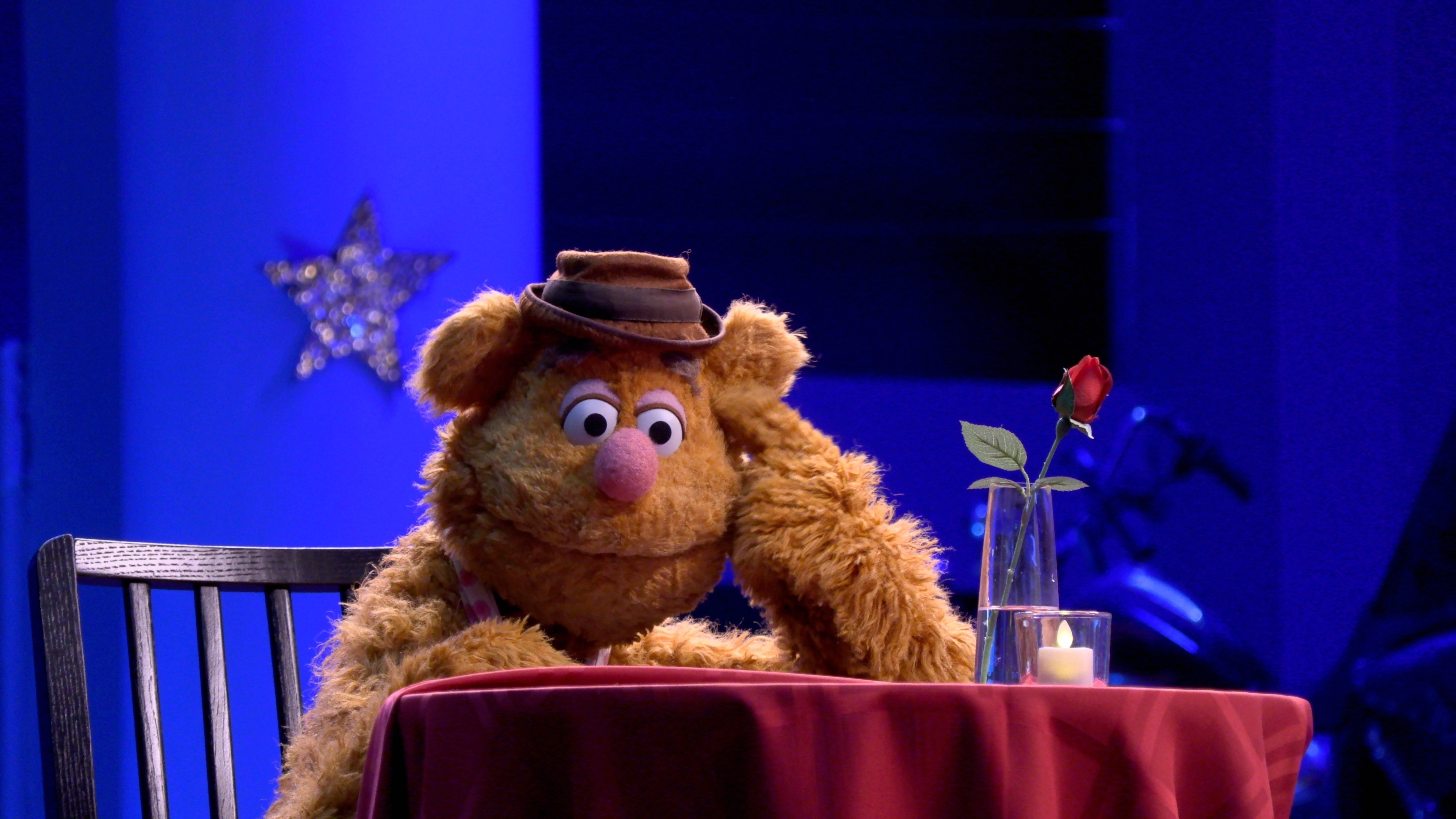 From the new Muppets Disney Plus show, Fozzie sits at table with a rose in a vase on it waiting for someone it's very sad!