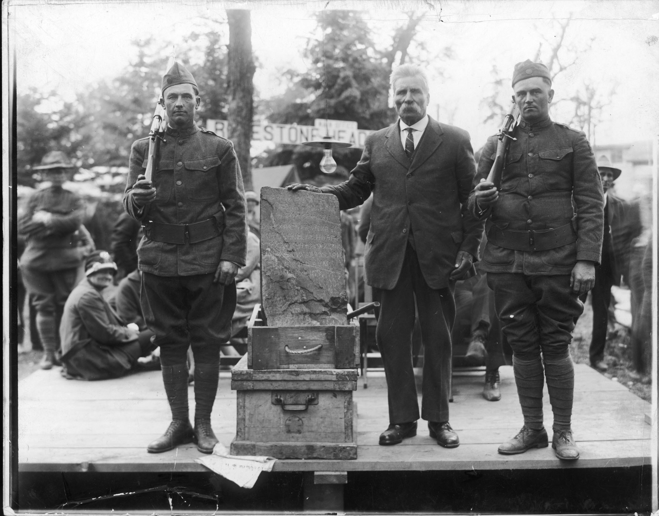 Olof Ohman, in tie, and the Kensington Runestone are flanked by armed guards at an exhibition in about 1929. Ohman said he found the buried stone on his Minnesota farm.