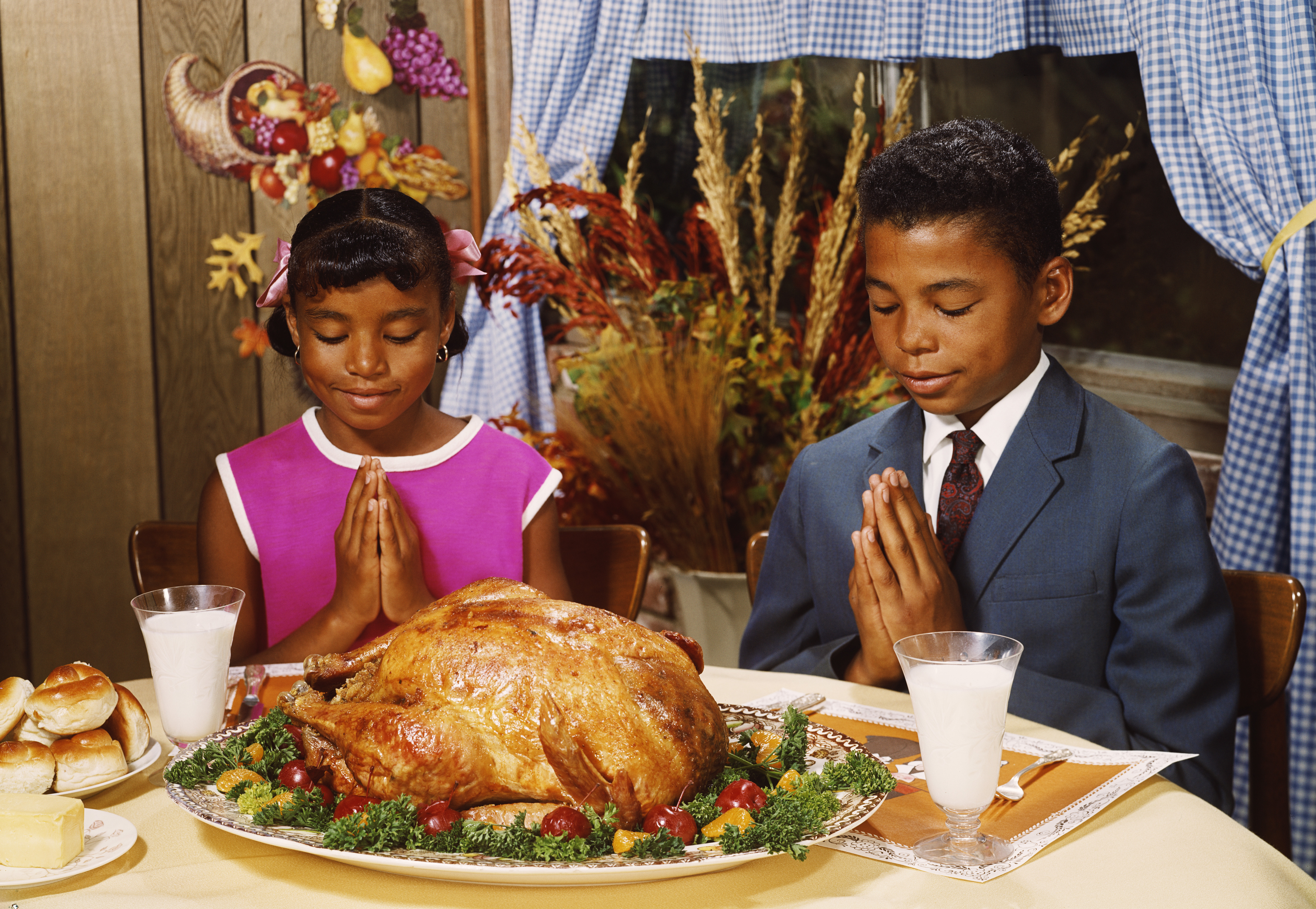 Image of the 1970s of a boy and girl saying grace at the dinner table with turkey in front of them.