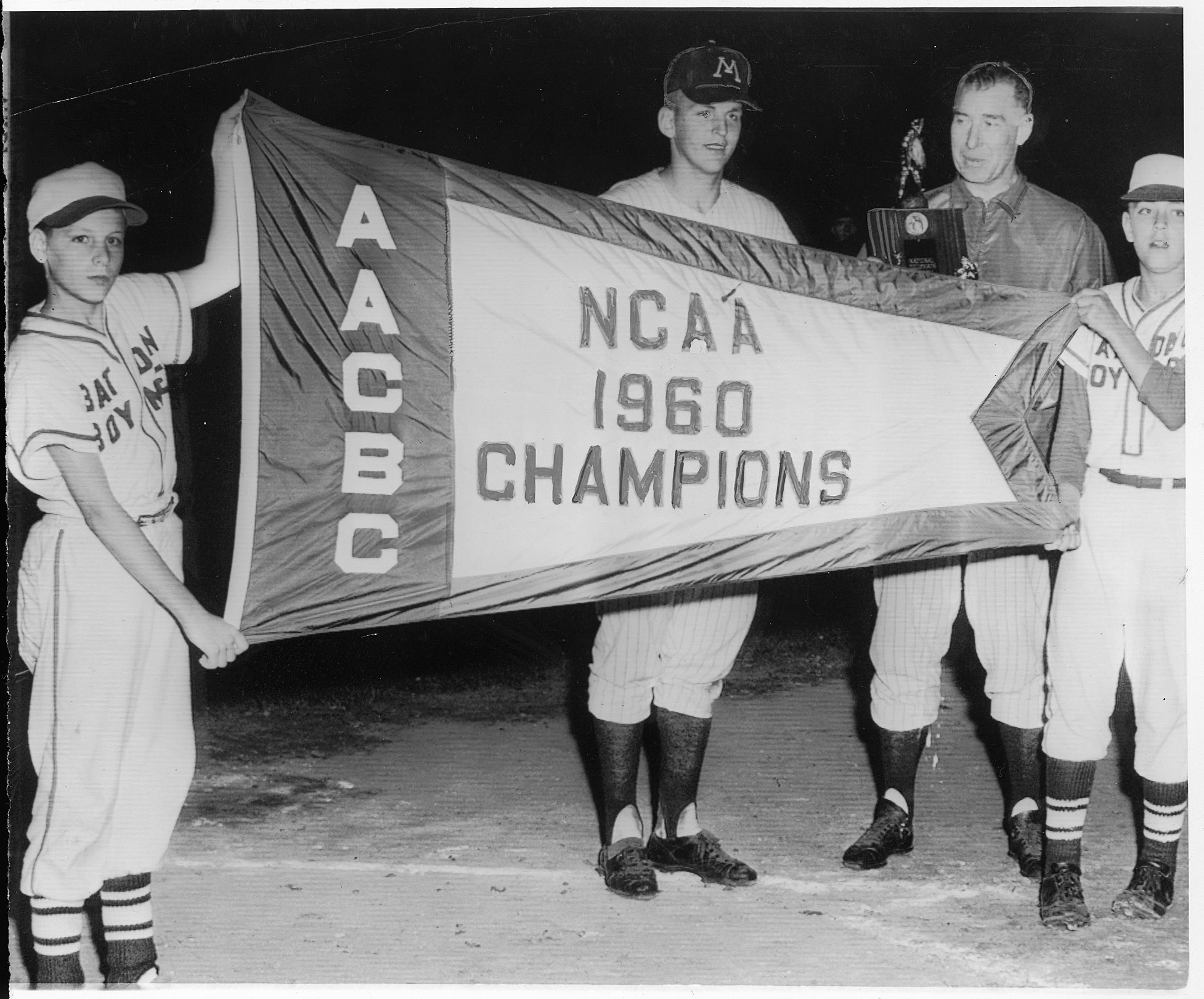 Batboys Don Noel and Dave Benson held up a 1960 NCAA championship flag for Gophers team MVP John Erickson and coach Dick Siebert.