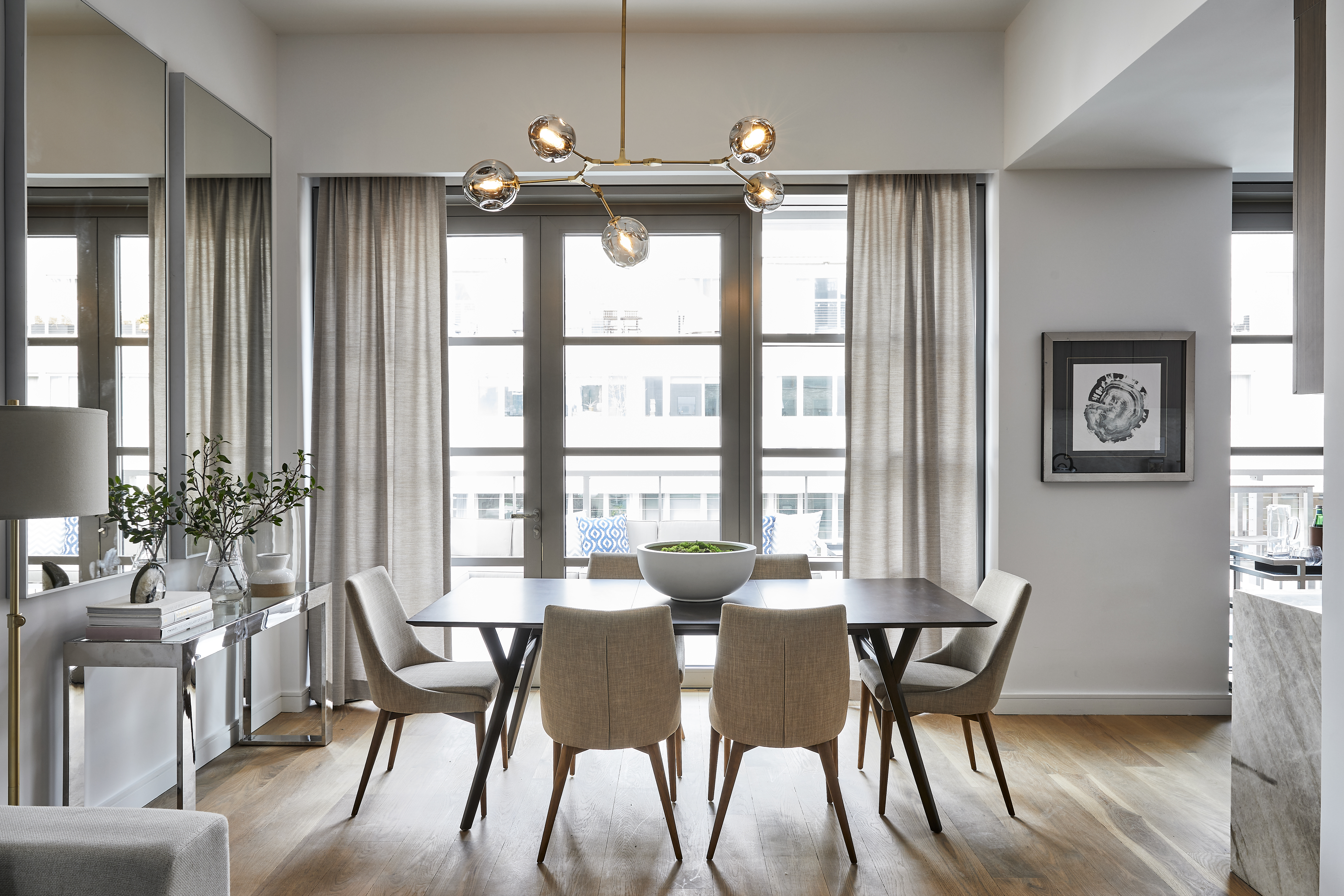Mirrors hung vertically in this dining space help add light and create the illusion of an additional set of windows.
