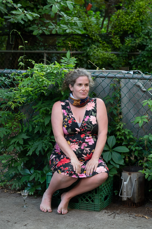 A pregnant woman in a sleeveless floral dress sits on a green crate against a fence with green plants surrounding her.