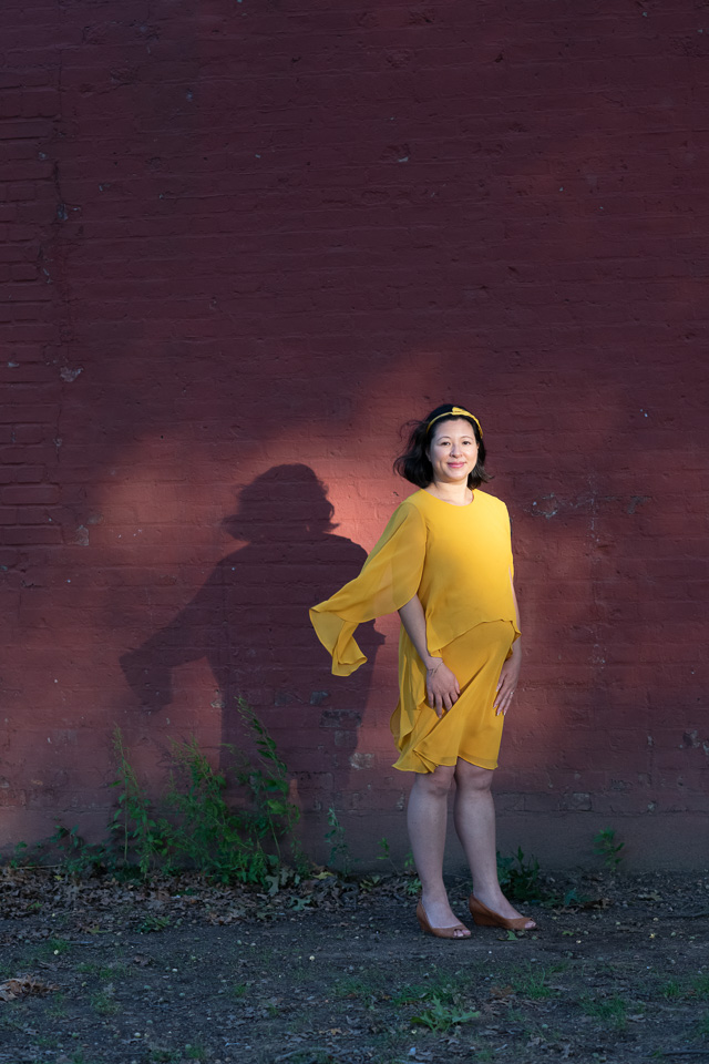 A pregnant woman wearing a yellow dress stands outdoors in warm light against a red brick wall.