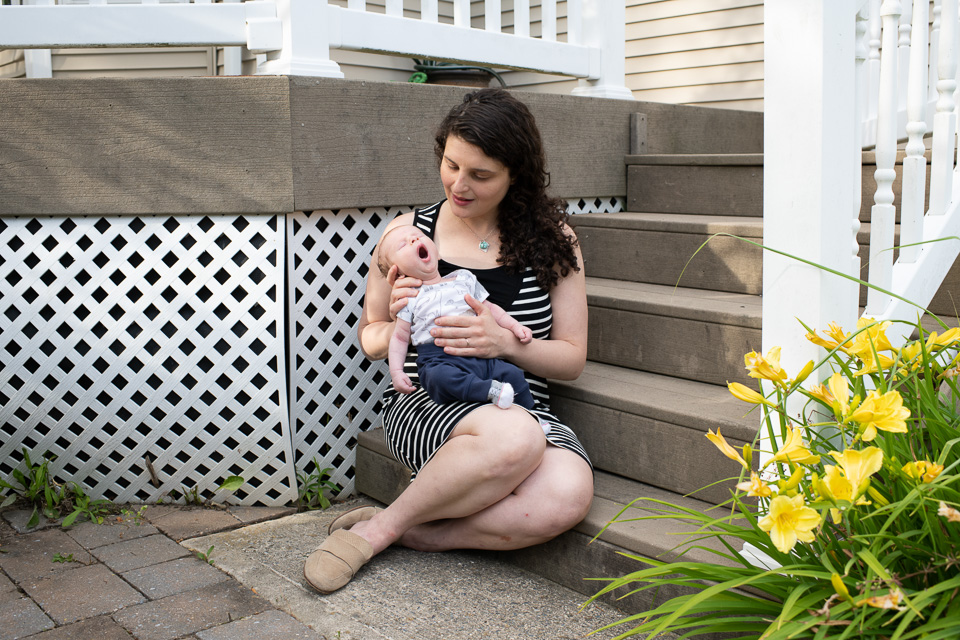 A woman in a striped dress sits at the bottom of porch steps holding a small, yawning baby in her lap.