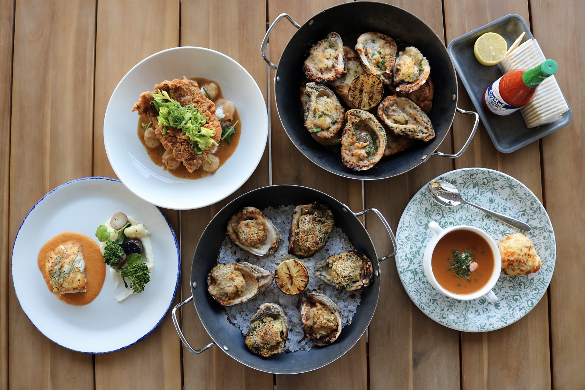 Oysters, seafood bisque, and other seafood dishes on a wood table