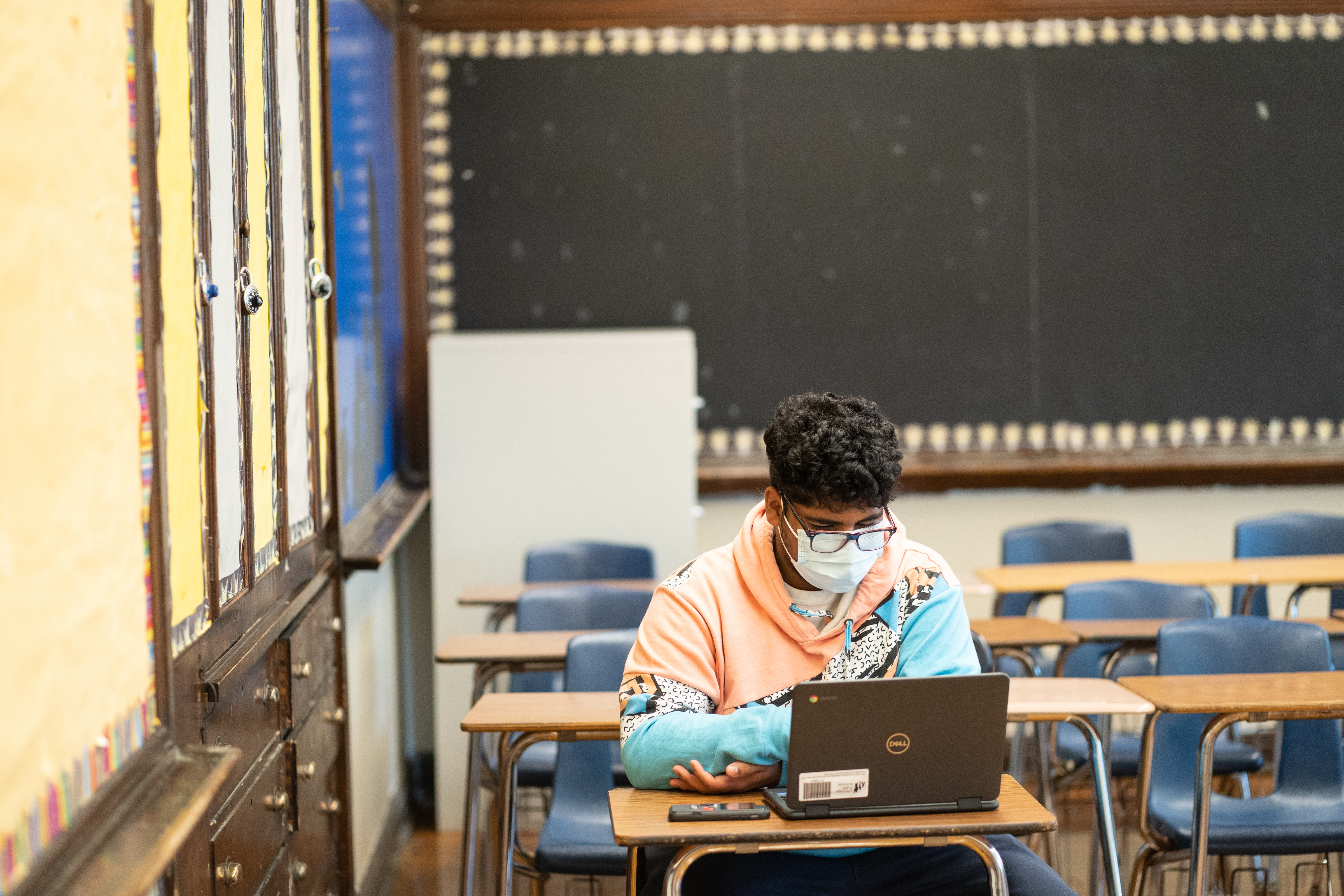 High school student Nathaniel Martinez, in a mask and orange and blue-colored hoodie, sits at a desk with a laptop in a Roosevelt High School classroom full or other empty desks and a chalkboard on the wall in the back.