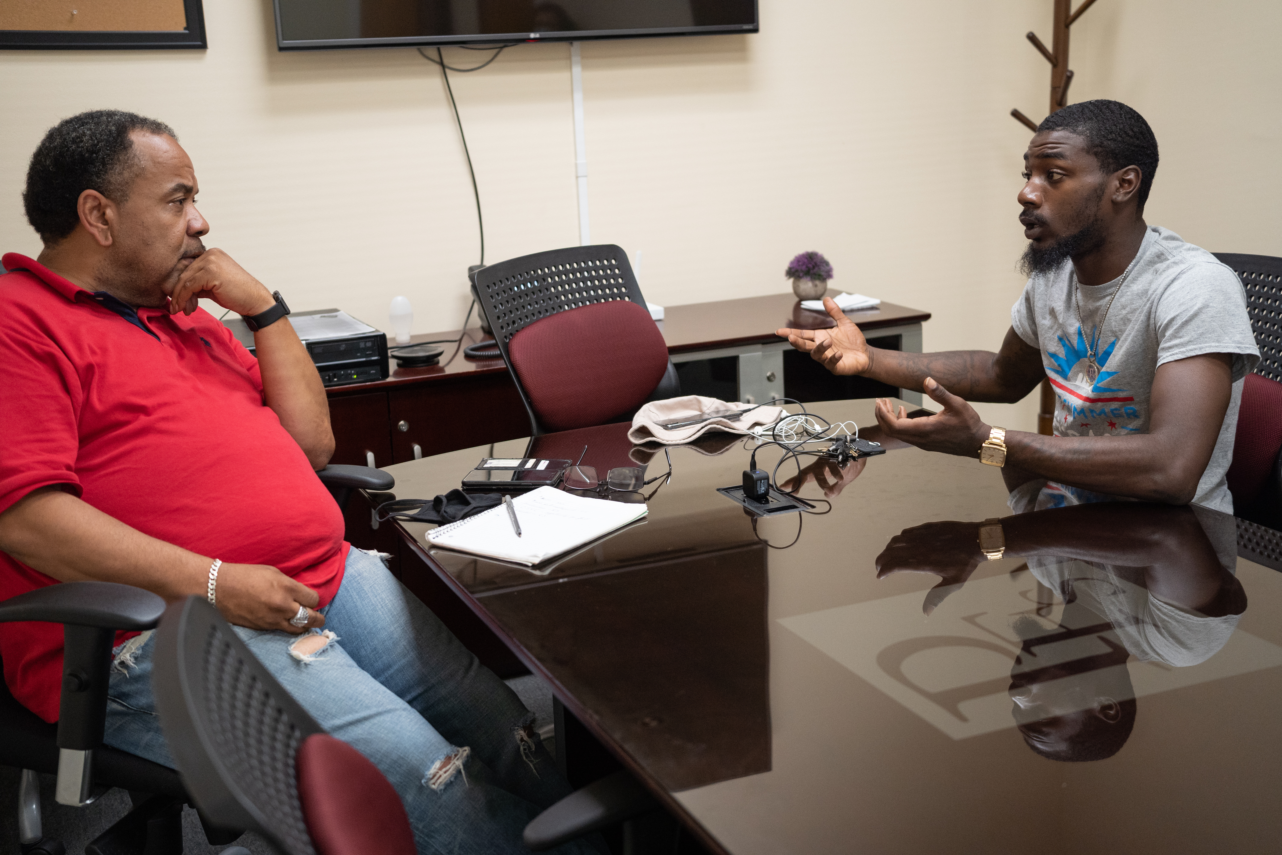 Sidney Johnson in a red shirt and jeans sits at a desk at the Roseland Reconnection Hub in Chicago and mentors Ti'Shawn Clark, who sits on the other side of the desk.