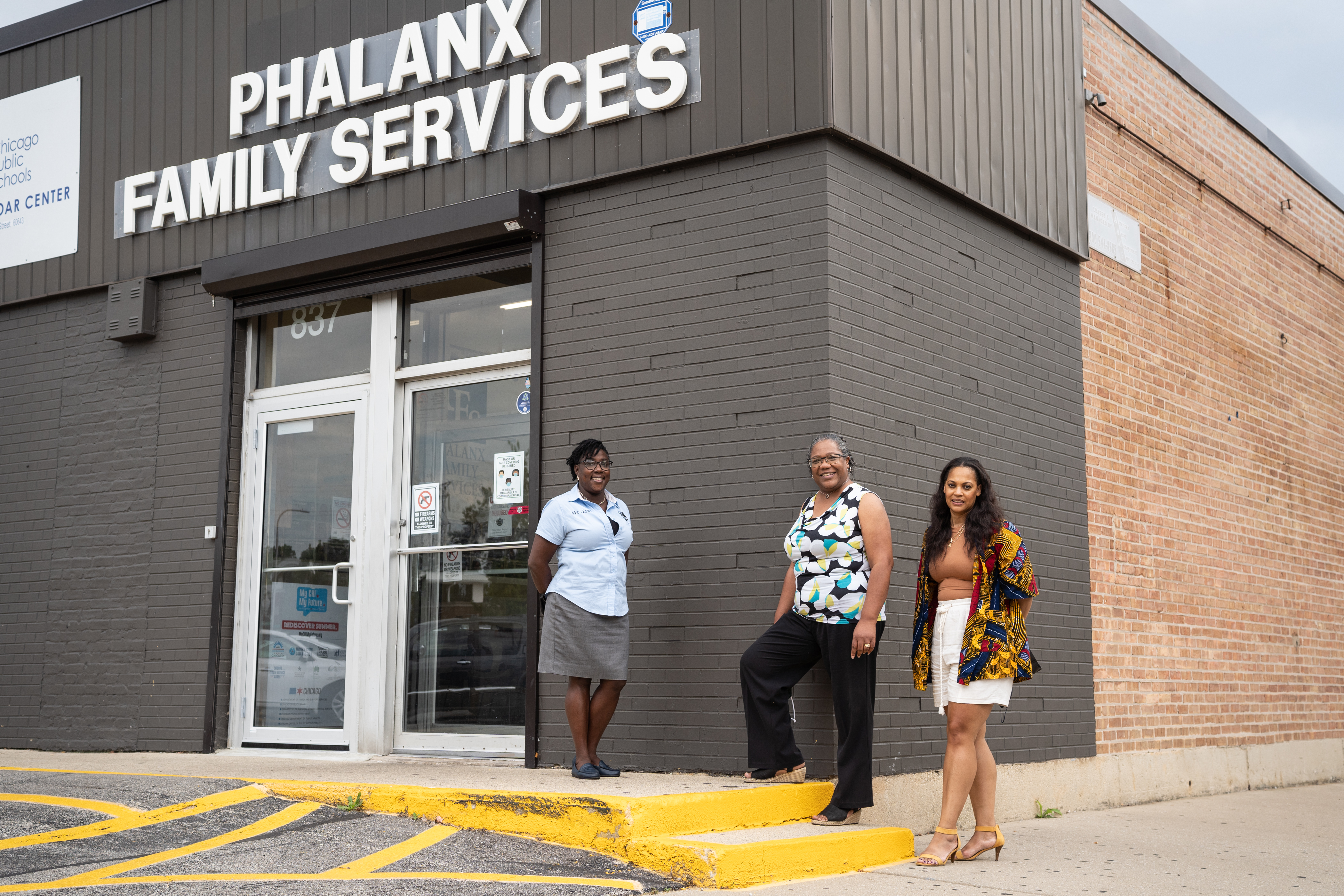 Roseland Reconnection Hub leaders Pauline Sylvain-Lewis and Laura Bailey, and Iona Calhoun-Battiste of Thrive Chicago stand outside a gray brick building with the words Phalanx Family Services above the entrance door.