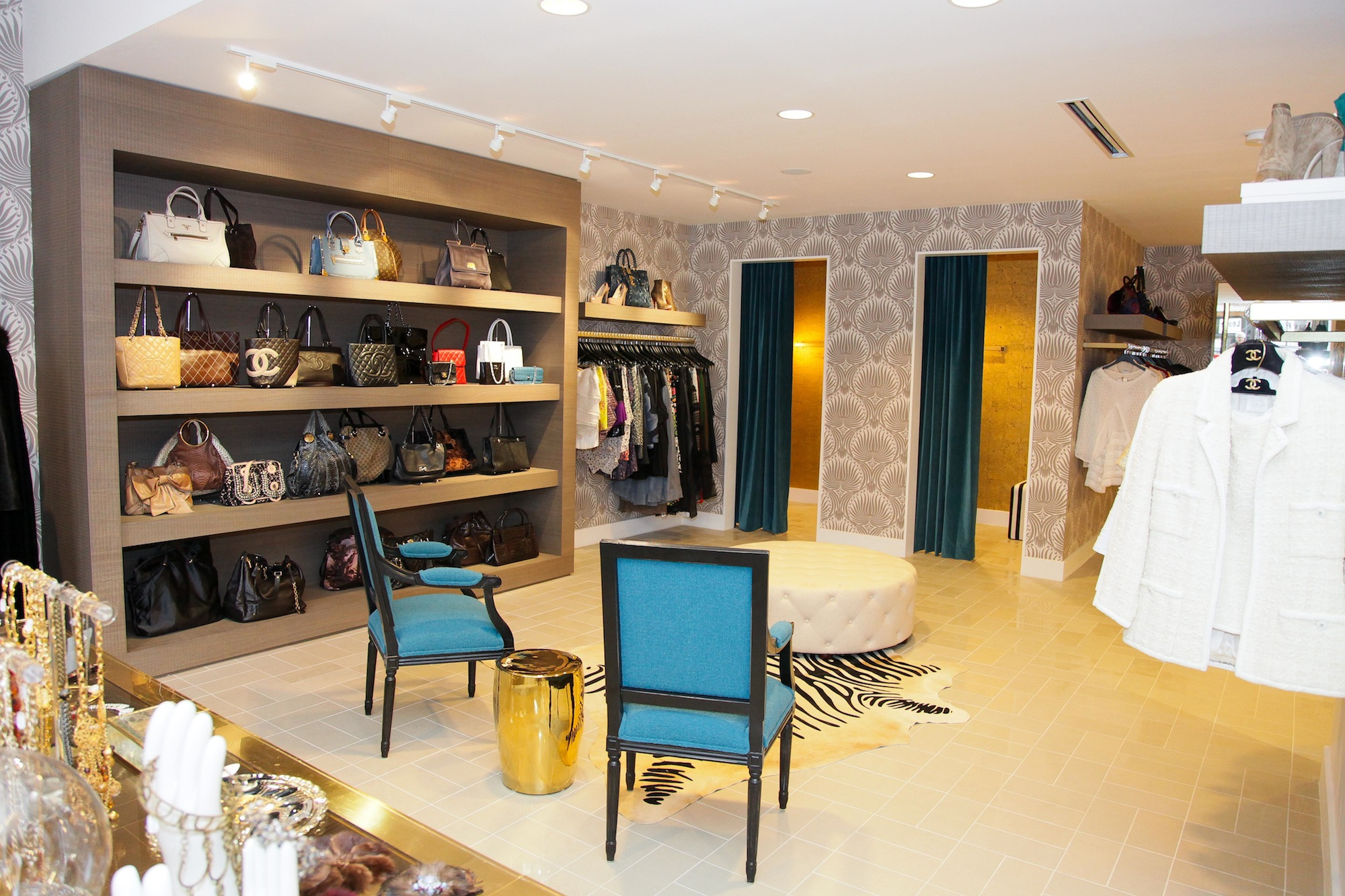 the first photos of luxury garage sale the brick mortar on the far wall are handbags in a built in wall fixture a seating area with a tufted white leather ottoman and a zebra rug dressing rooms are in the back