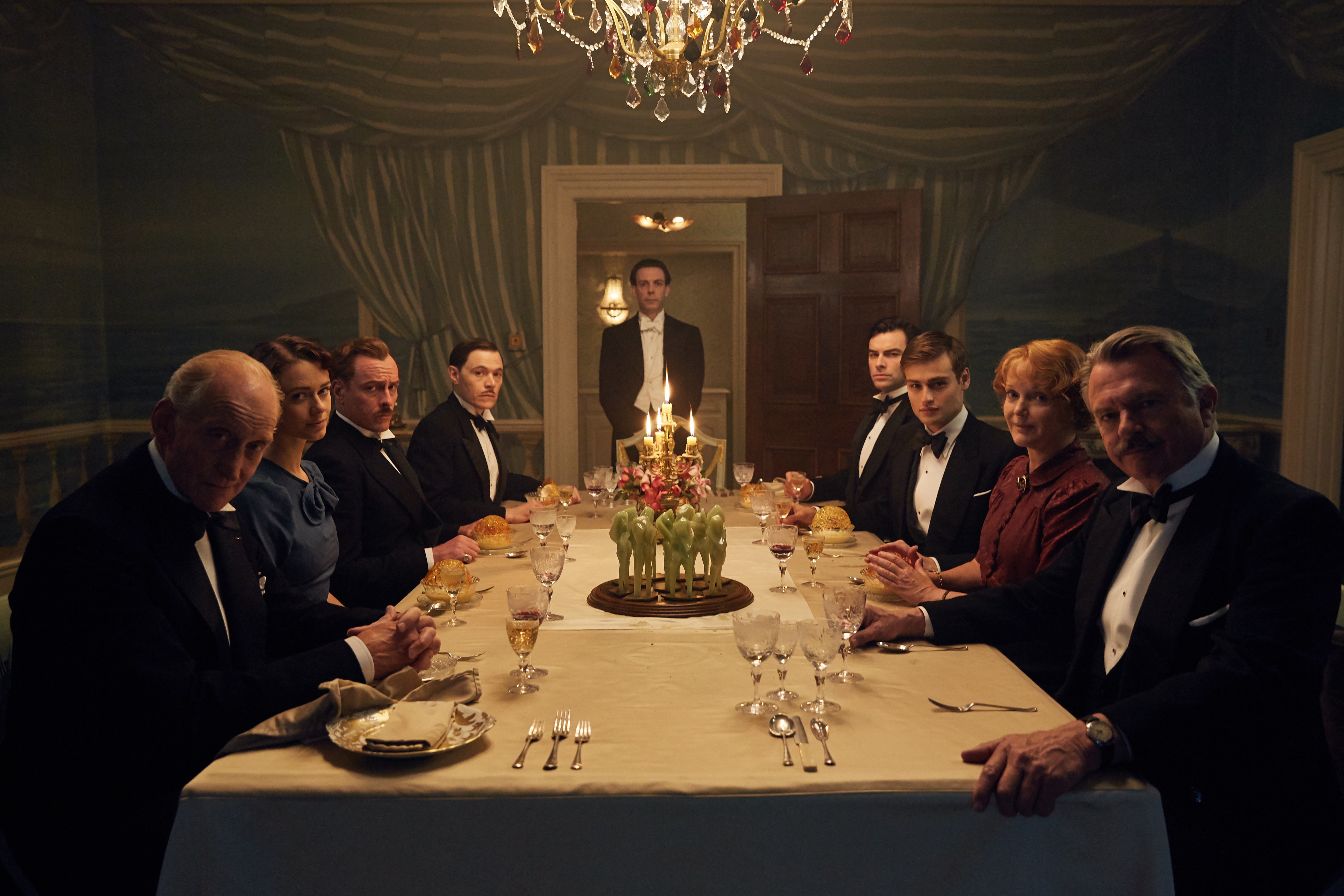 The Cast Of And Then There Were None Seated Around A Formal Dinner Table At