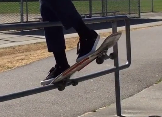 Skateboarder uses physics and/or wizardry to spin his board around a railing