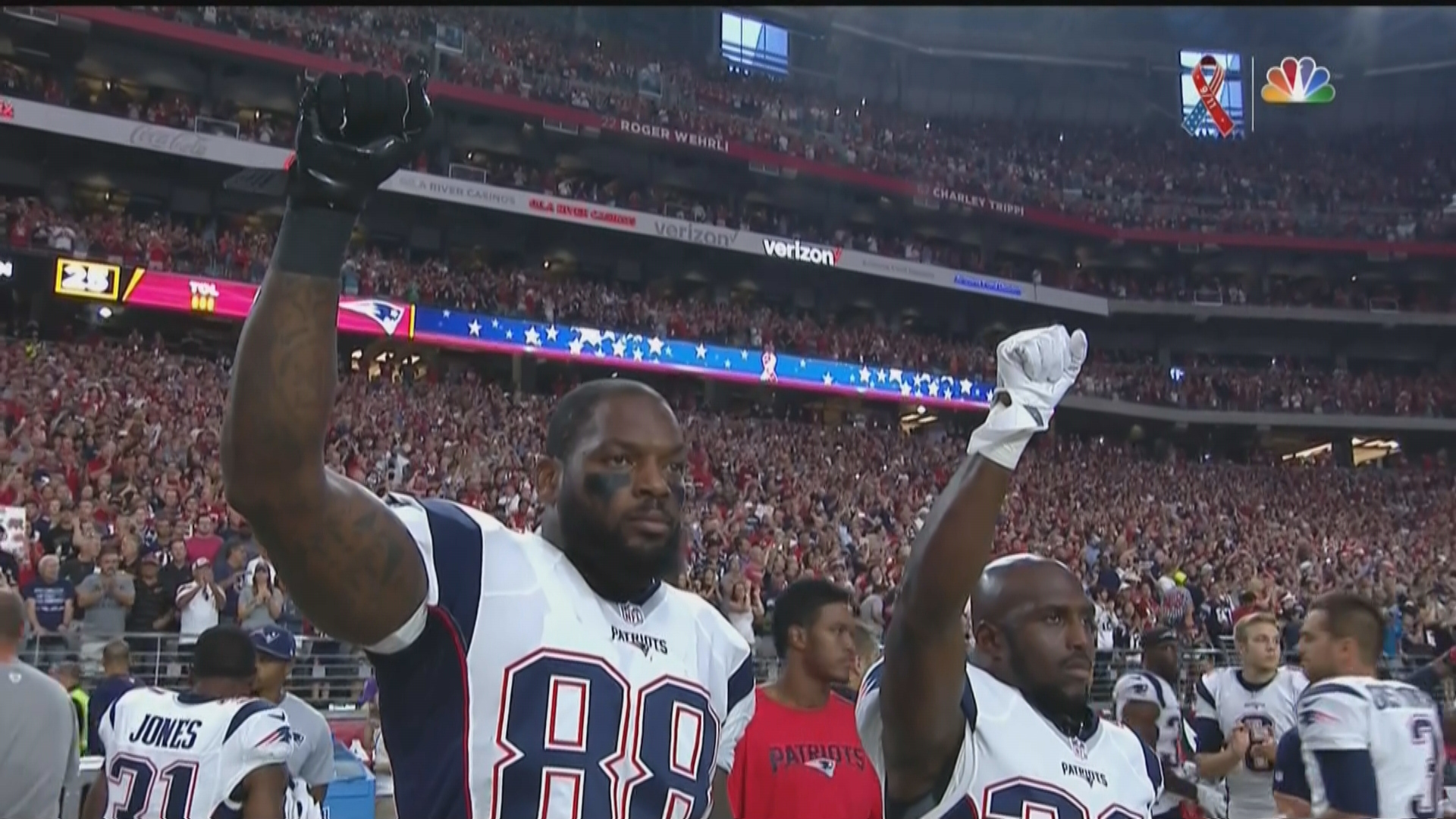 7a9f5bf6218 ... Patriots TE Martellus Bennett and DB Devin McCourty raise fists after  the national anthem