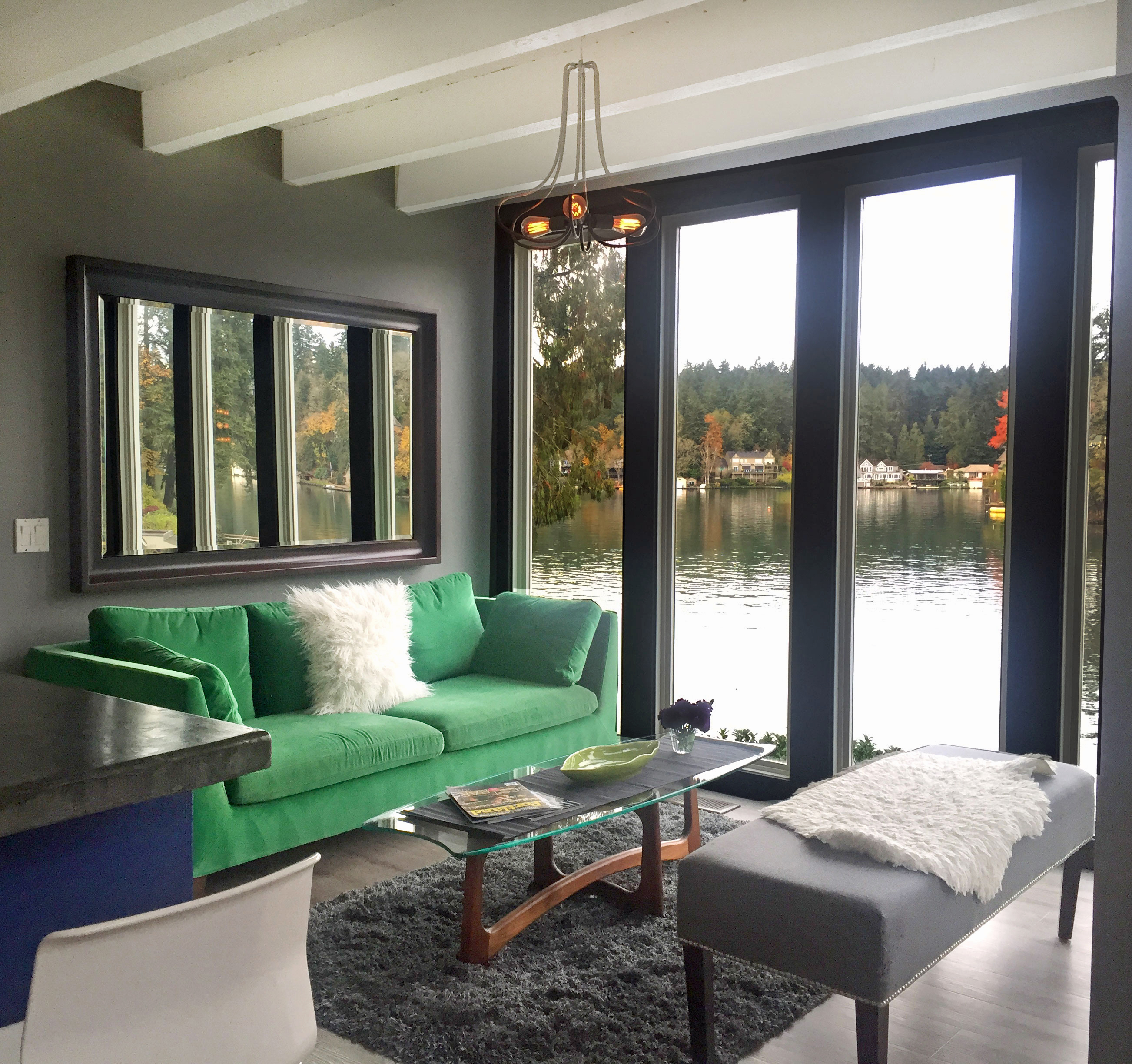A Bright Green Couch In A Living Room With Dark Grey Walls And Floor To