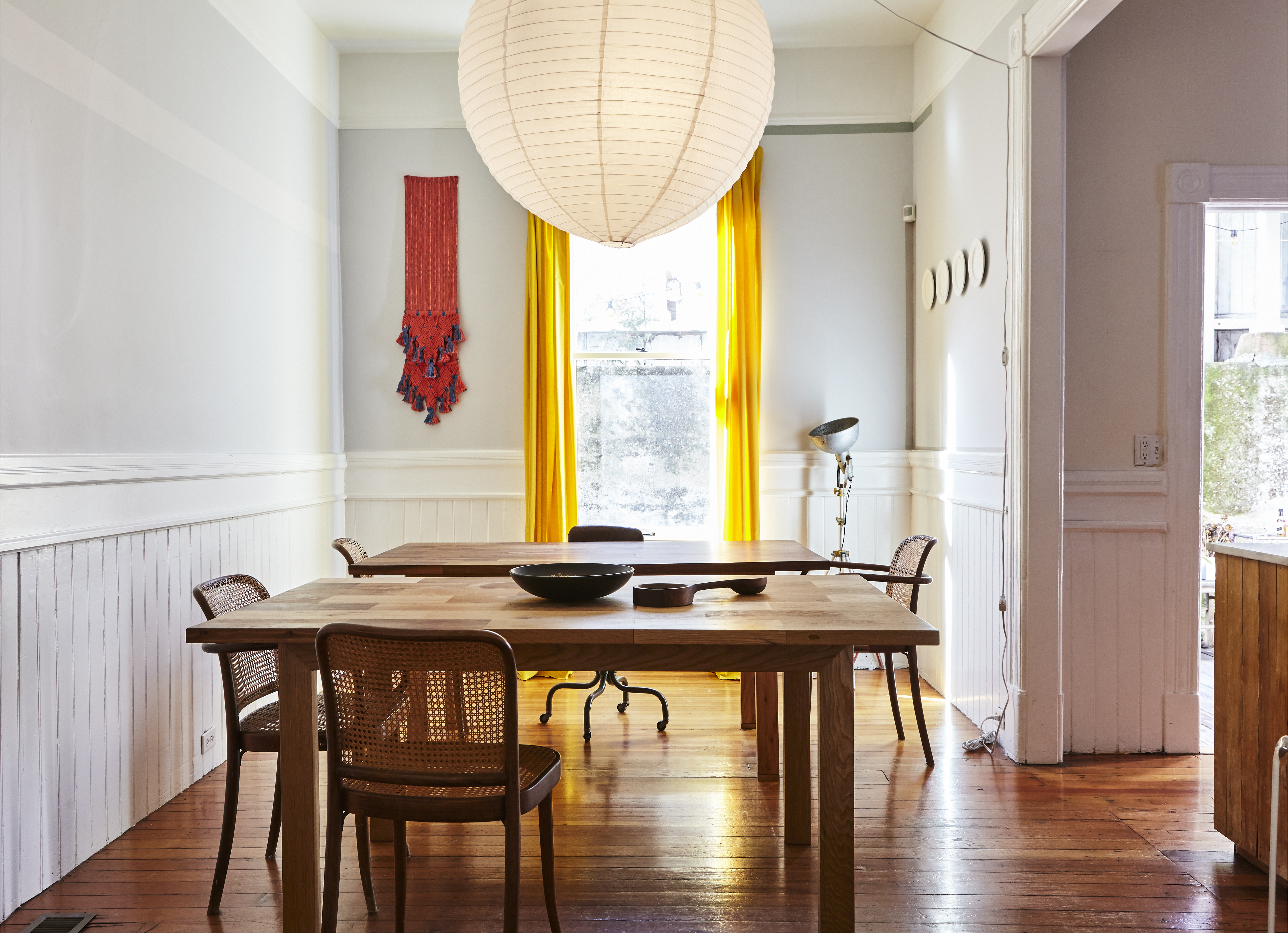Dining Room With Two Large Wooden Tables, Yellow Curtains And Red Art Wall  Hanging.