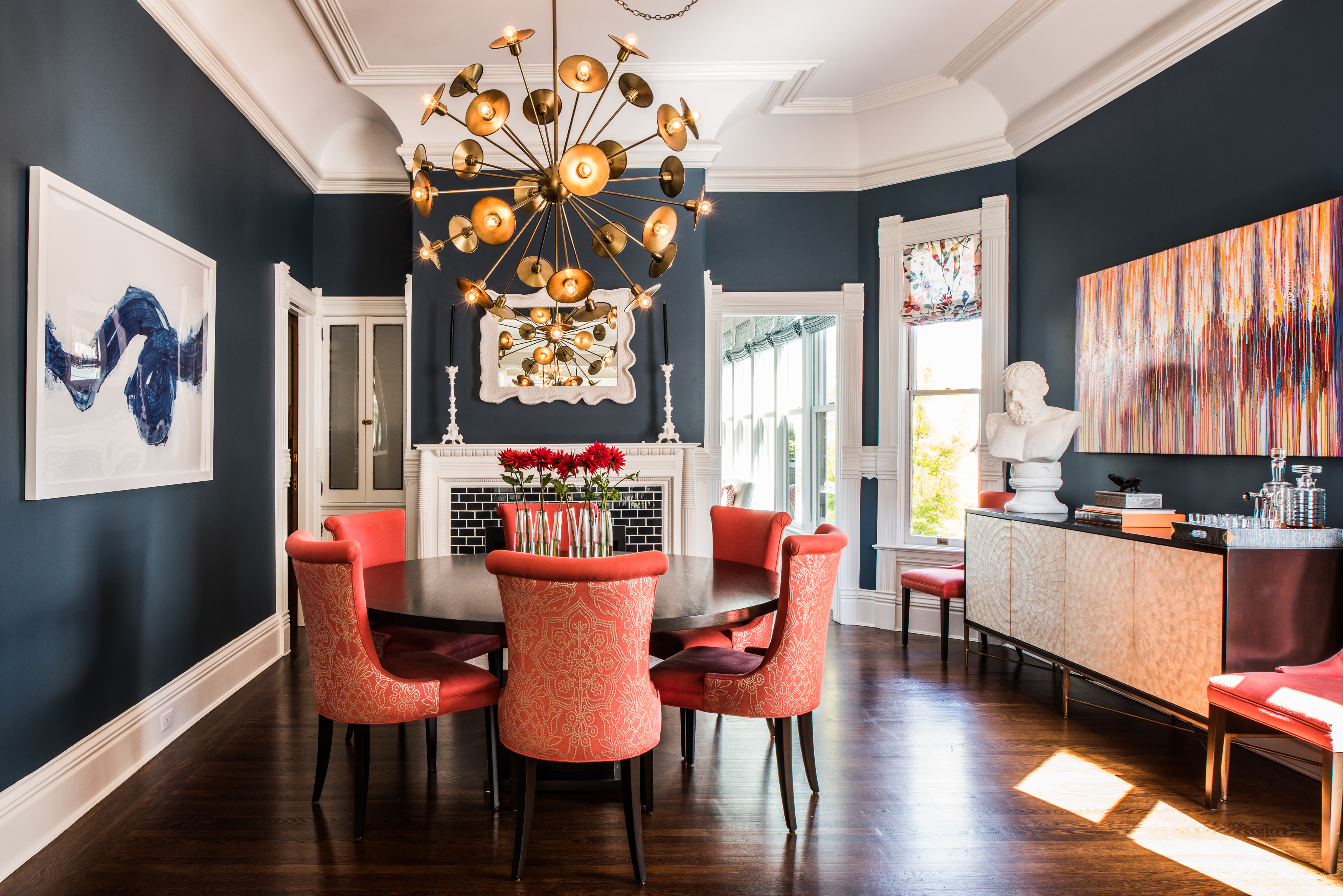 A Dark Blue Dining Room With Orange Accents.