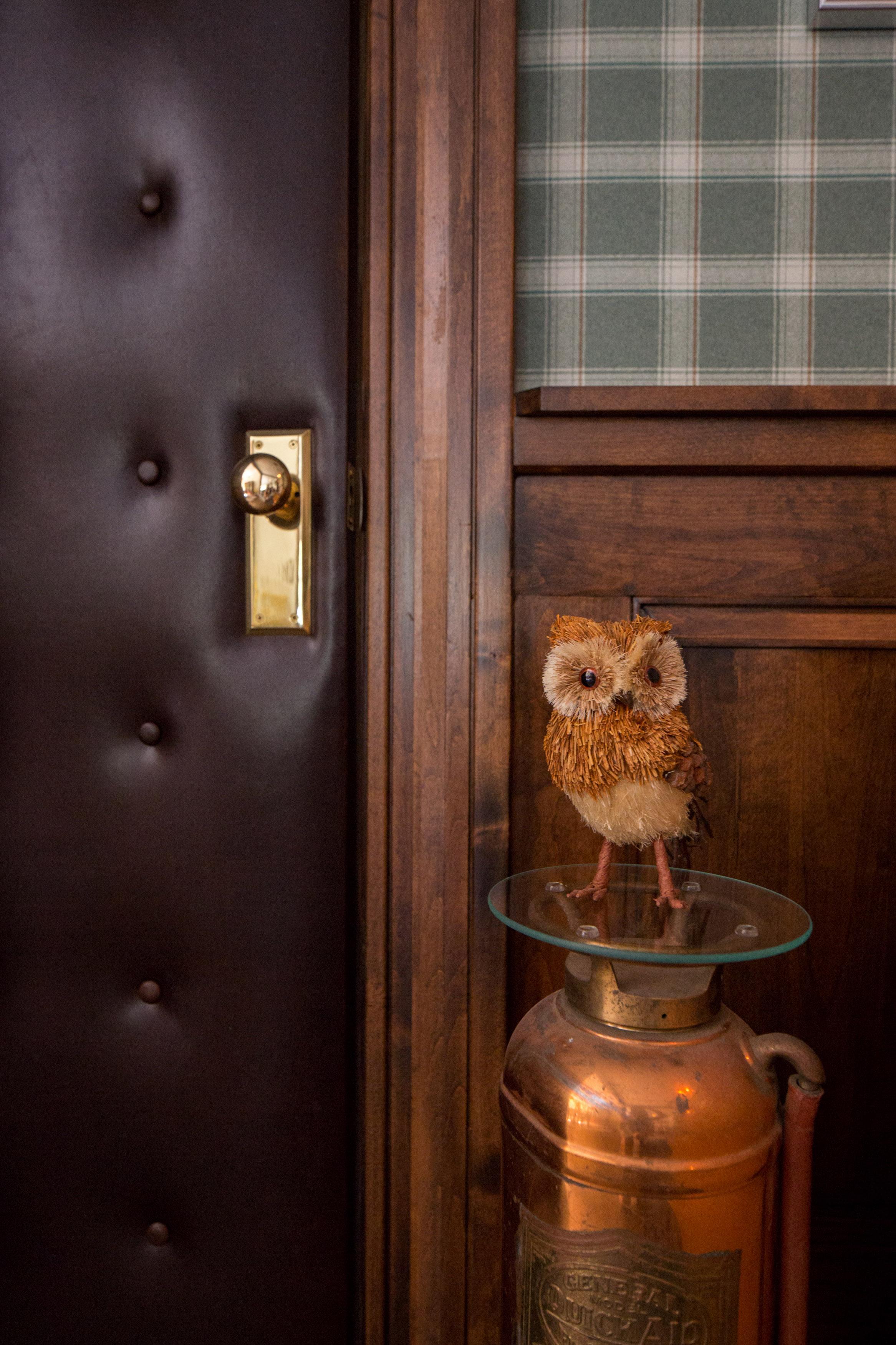 A Little Owl Rests On A Vintage Copper Fire Extinguisher.