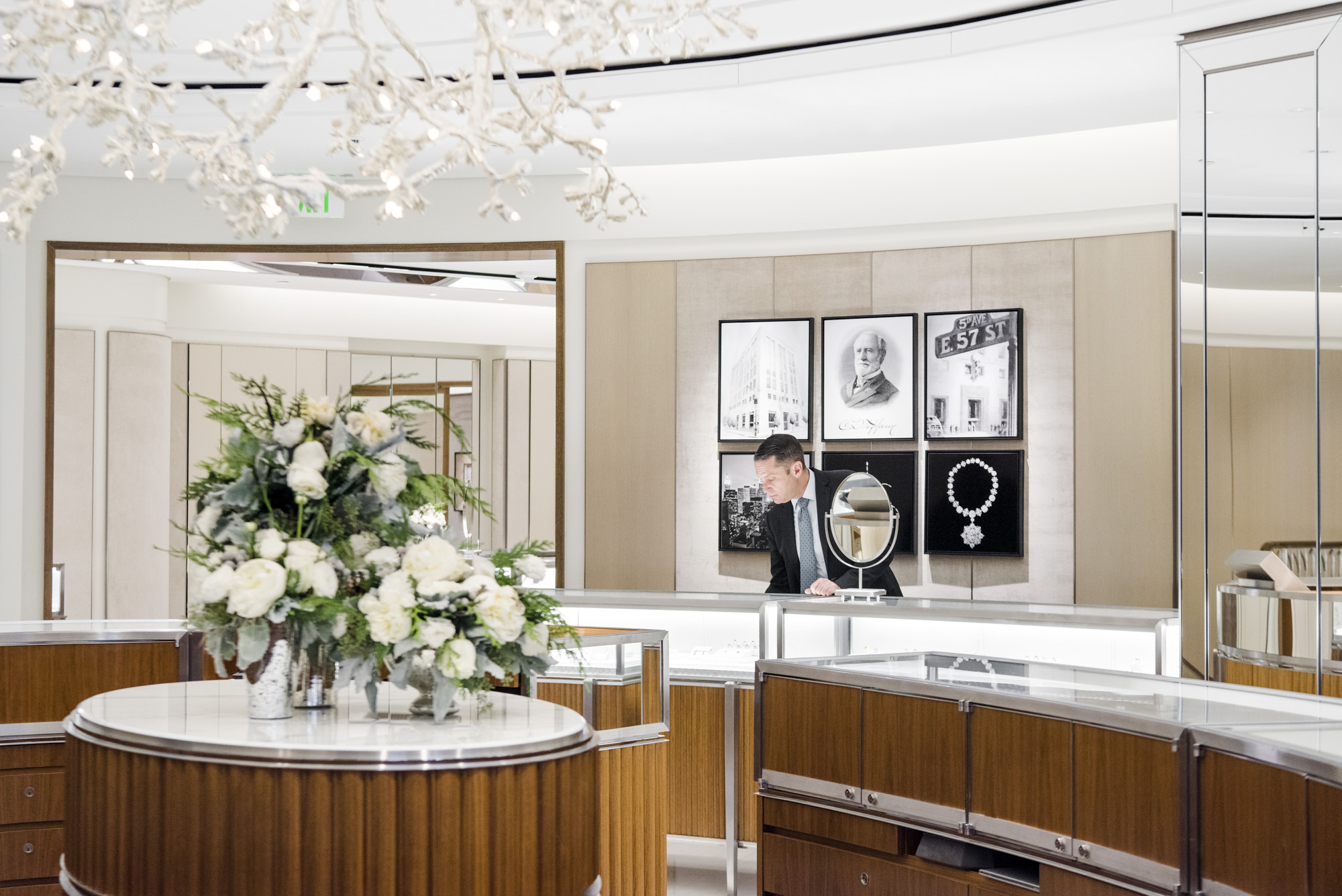 A Male Sales Associate At Tiffany Examines Jewelry Behind A Counter