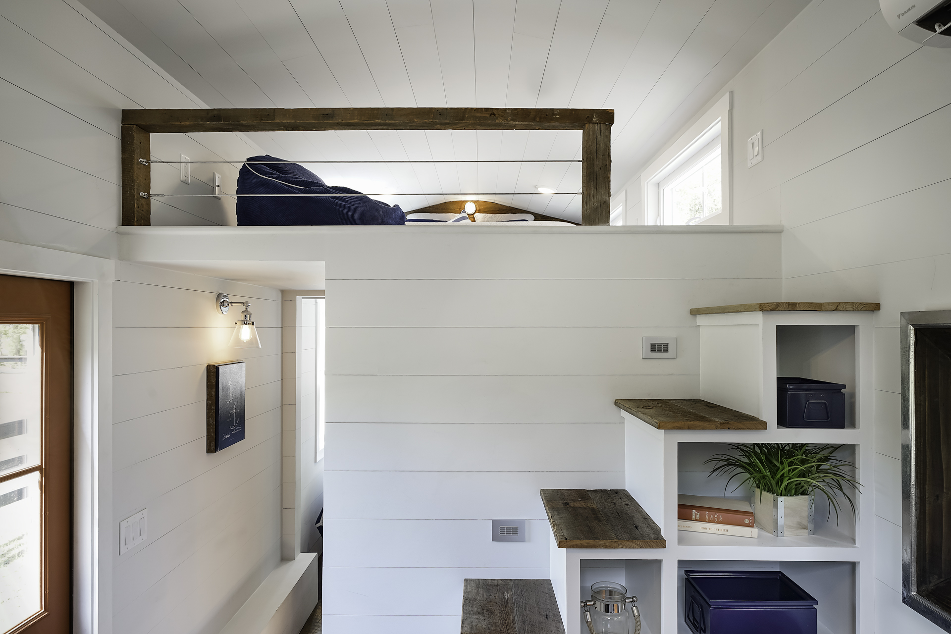 a tiny house with a separate bedroom that also turns into a workspace