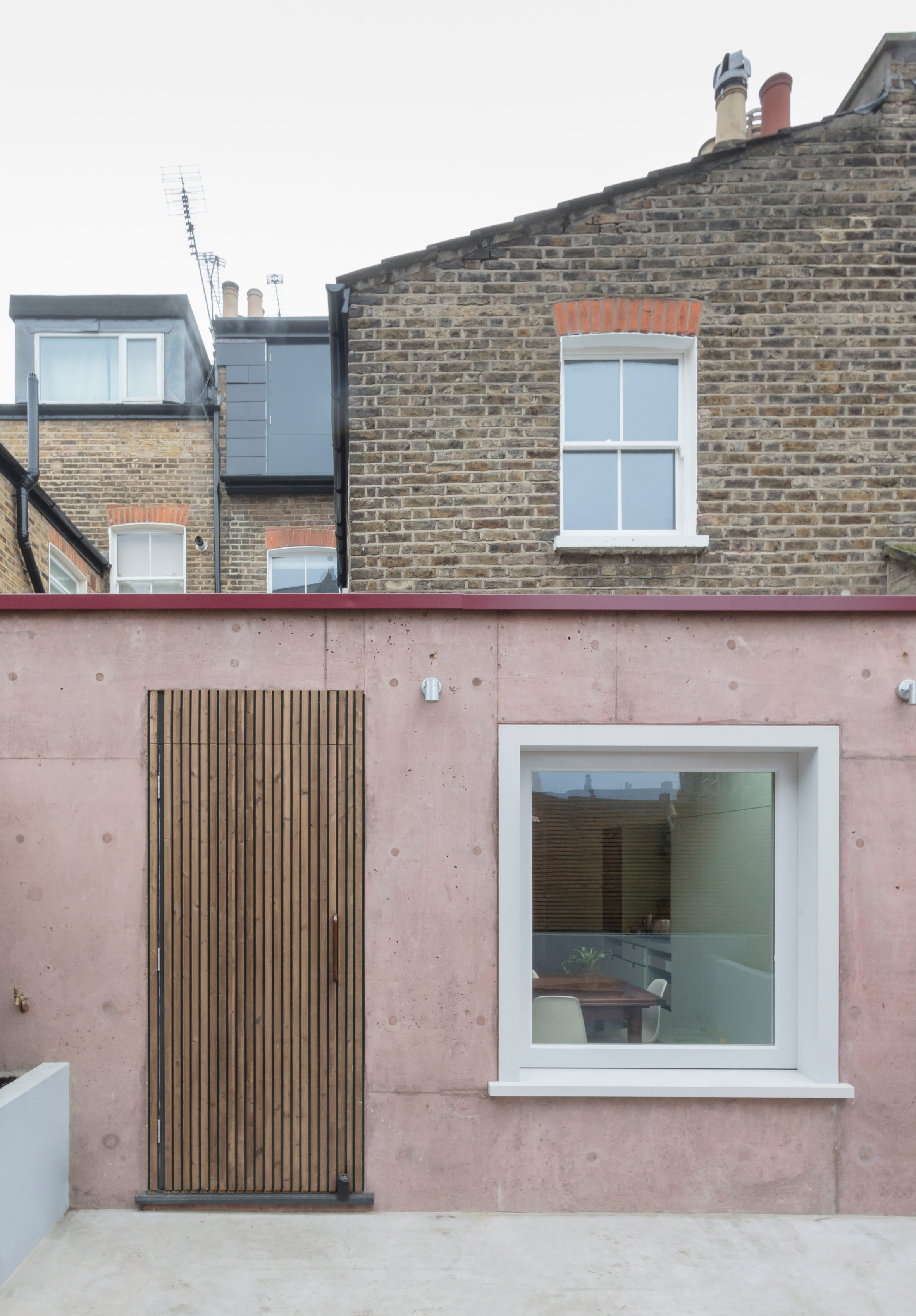 Pink Concrete Extension Adds Warmth And Texture To Brick