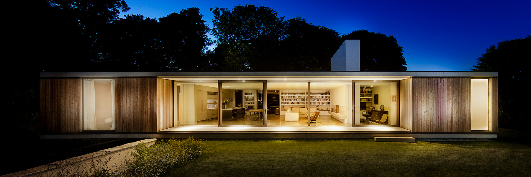 Modern house cantilevers over stone wall in England