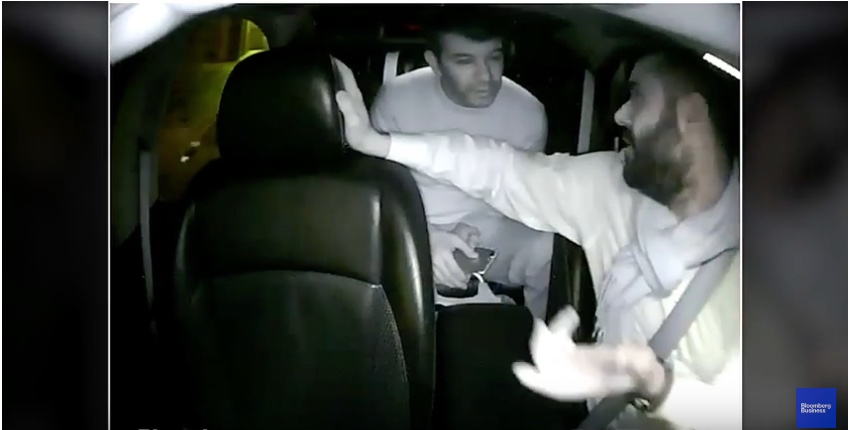 A video still of Travis Kalanick in the back seat of an Uber ride, talking to the driver