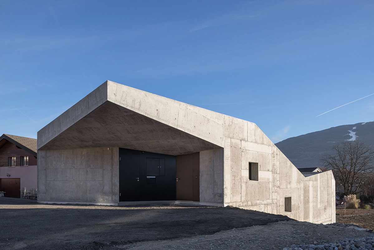 Concrete home climbs up small sloping site in switzerland for Half concrete half wood house design