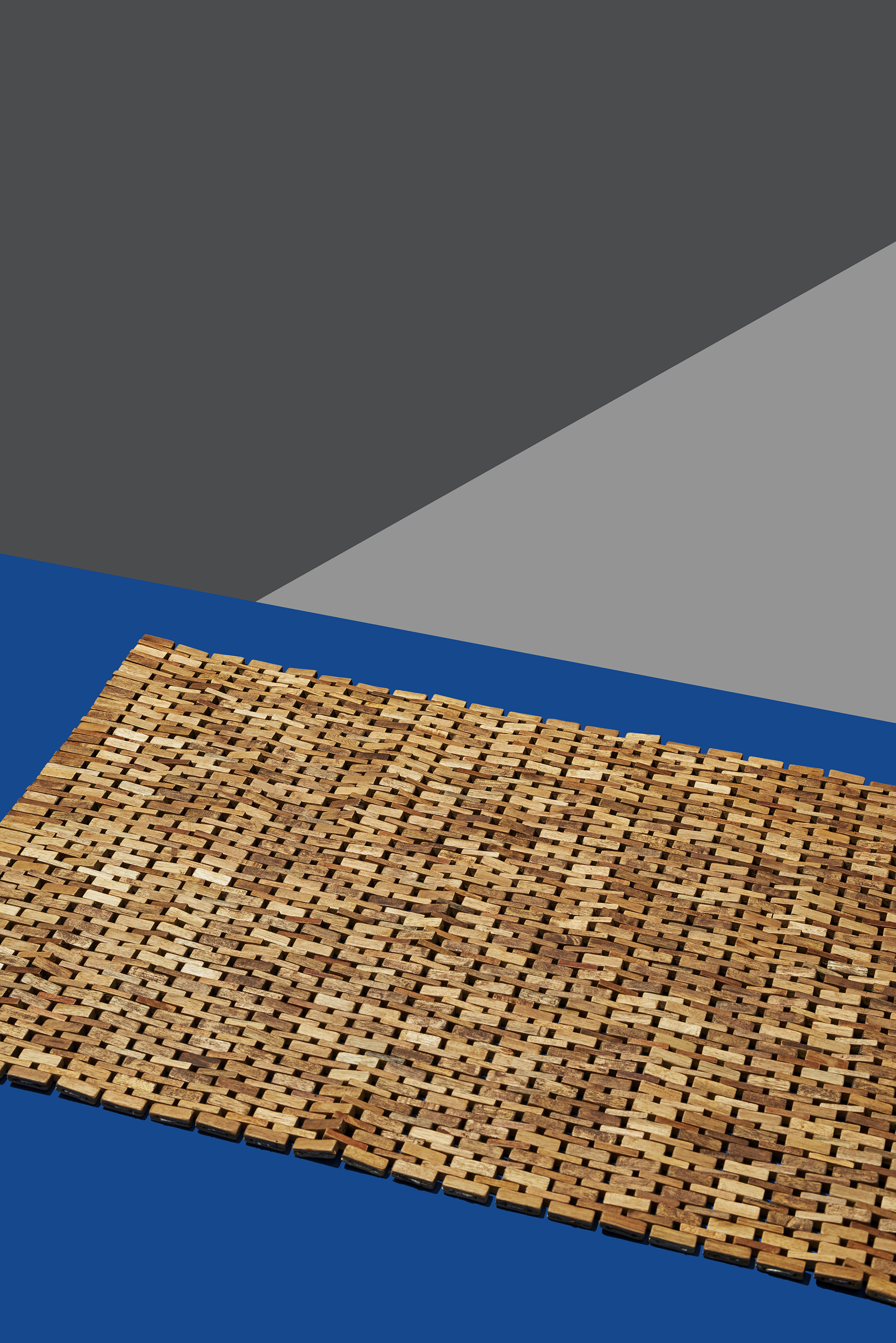A Woven Wood Bathroom Mat, By Crate And Barrel, On A Blue And