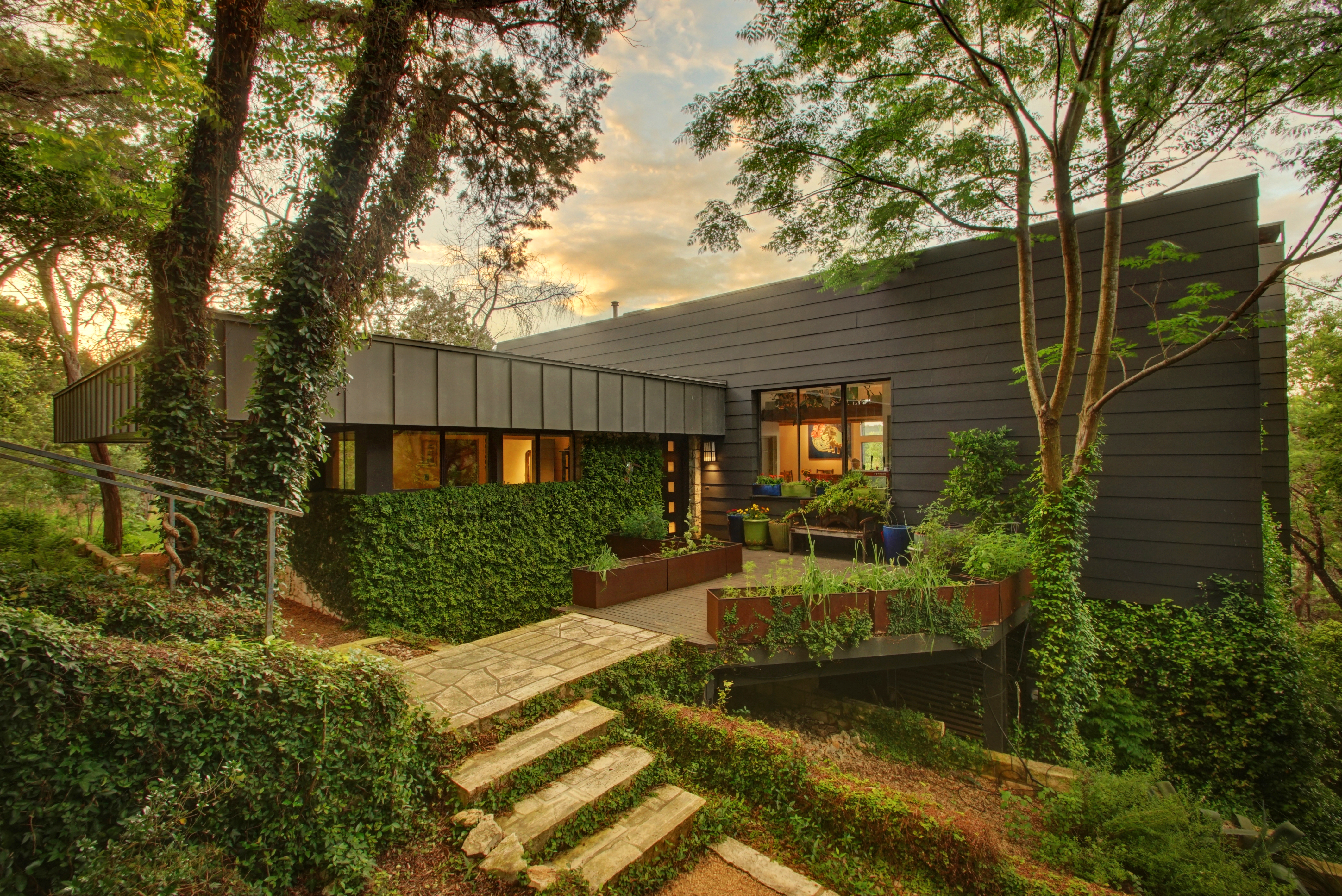 hidden home in west lake hills seeks 950k curbed austin 1992 boxy gray brown metal one story house with big patio surrounded by