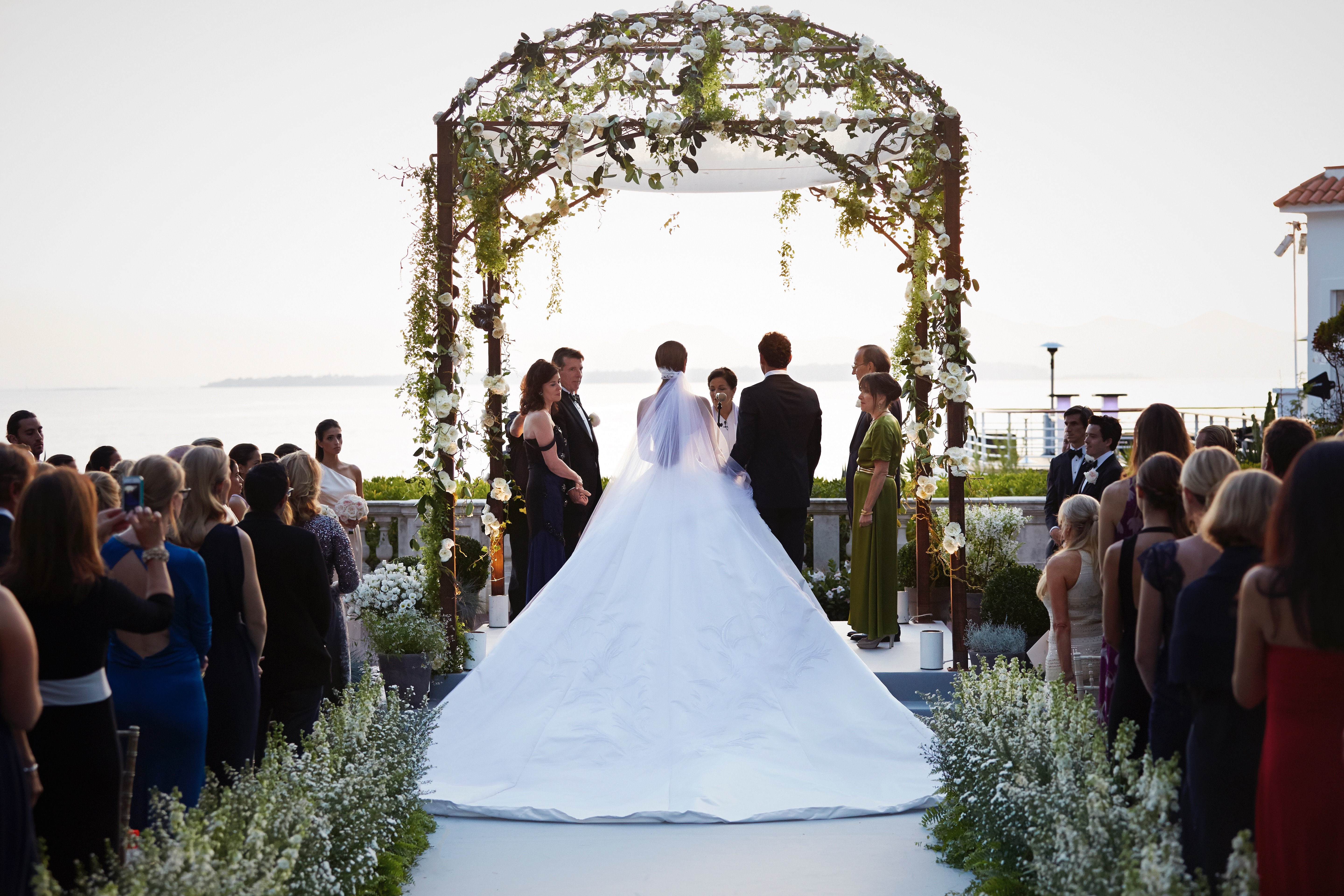 Nell and Teddy stand under the wedding huppah during the ceremony, which overlooks the Mediterranean