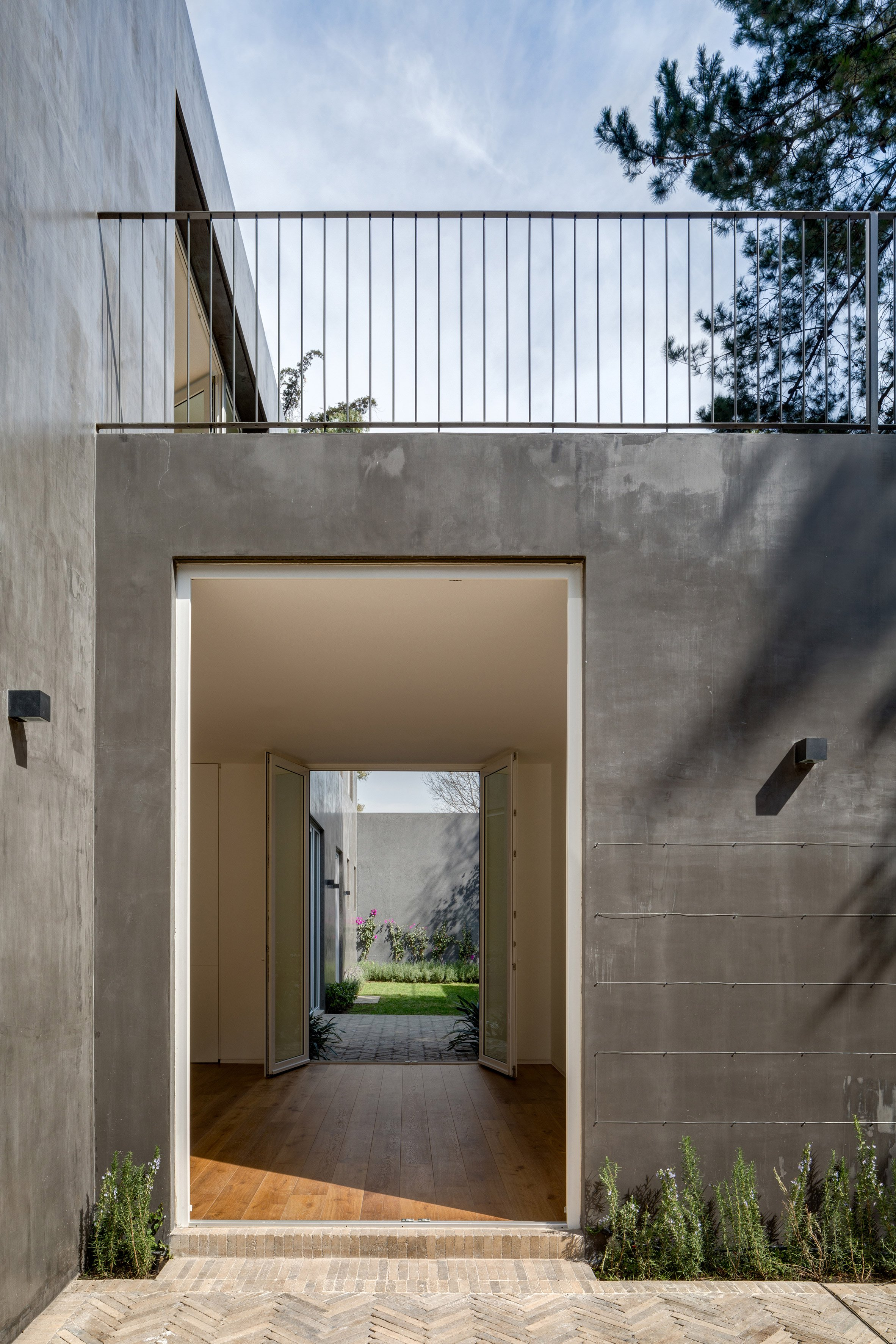 modern concrete home in mexico city unfurls around two courtyards the black finish contrasts starkly against the white interior walls and light hardwood floors creating a dynamic play between the traditional and the