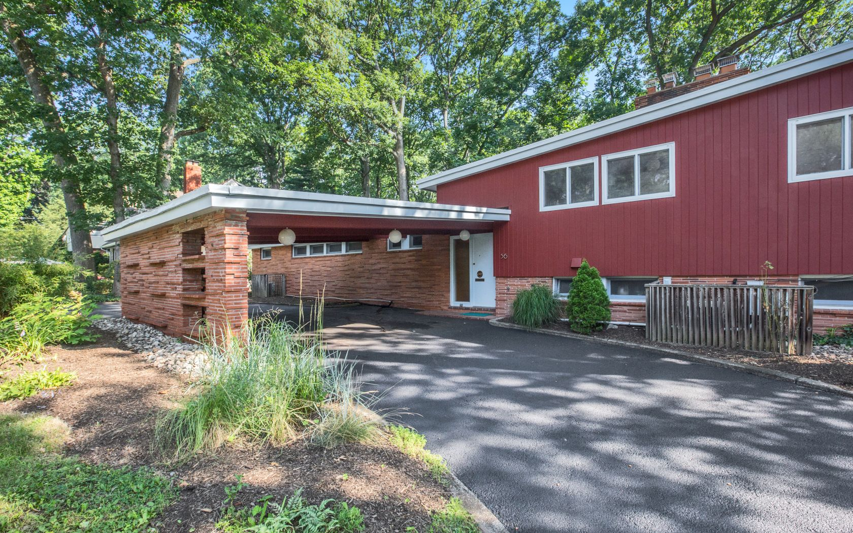 updated midcentury home with cork flooring asks 719k curbed measuring 2 700 square feet the split level home features a dynamic layout that includes an open plan living area with a massive brick fireplace and