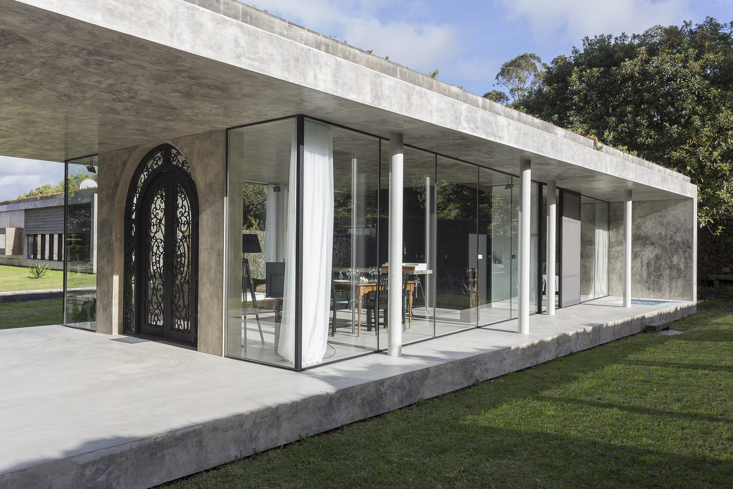 But while almost every architectural detail of the home reflects a raw modernist truth to materials ethos the front door looks like its from a different