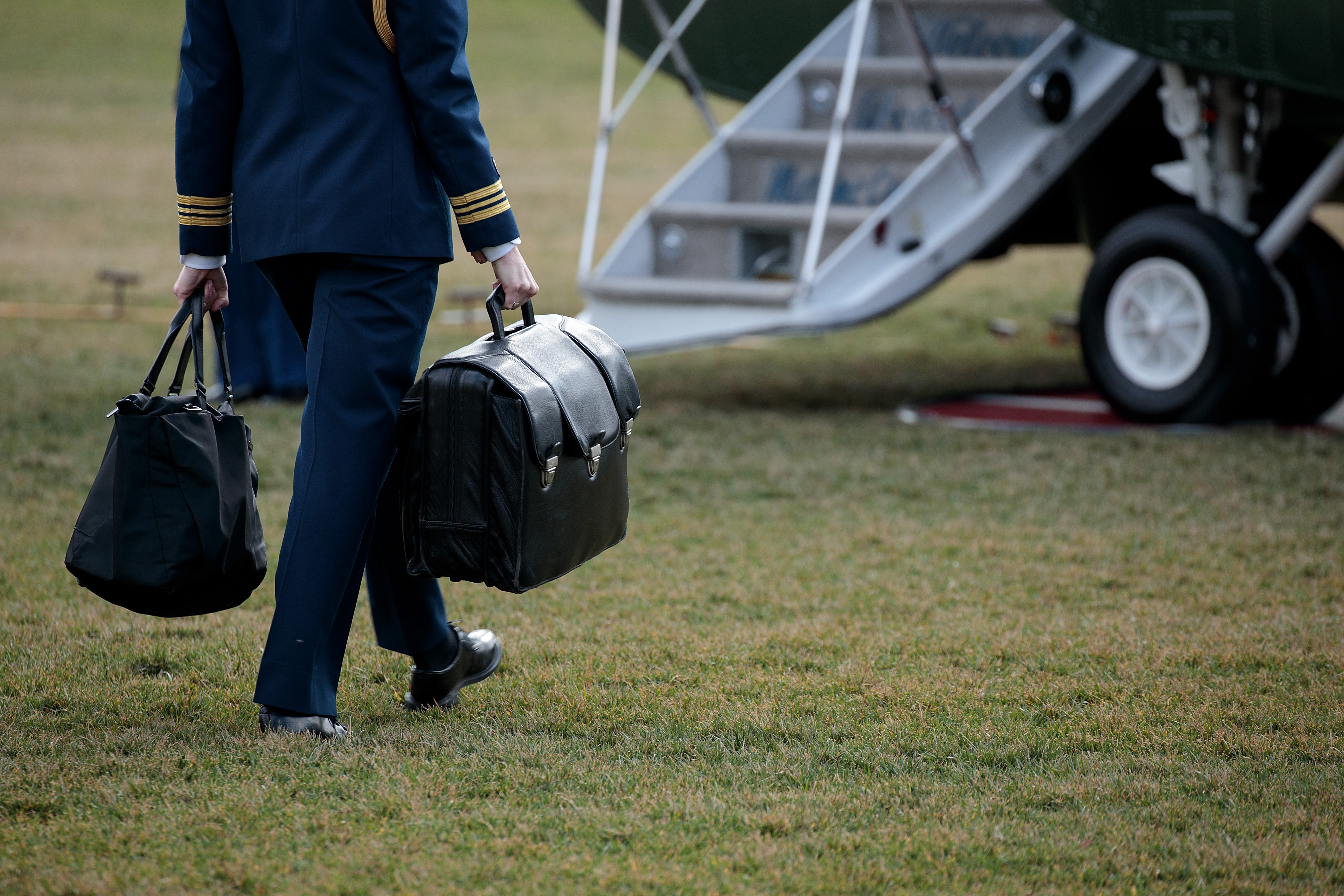 An officer carries a large black briefcase and walks toward an airplane