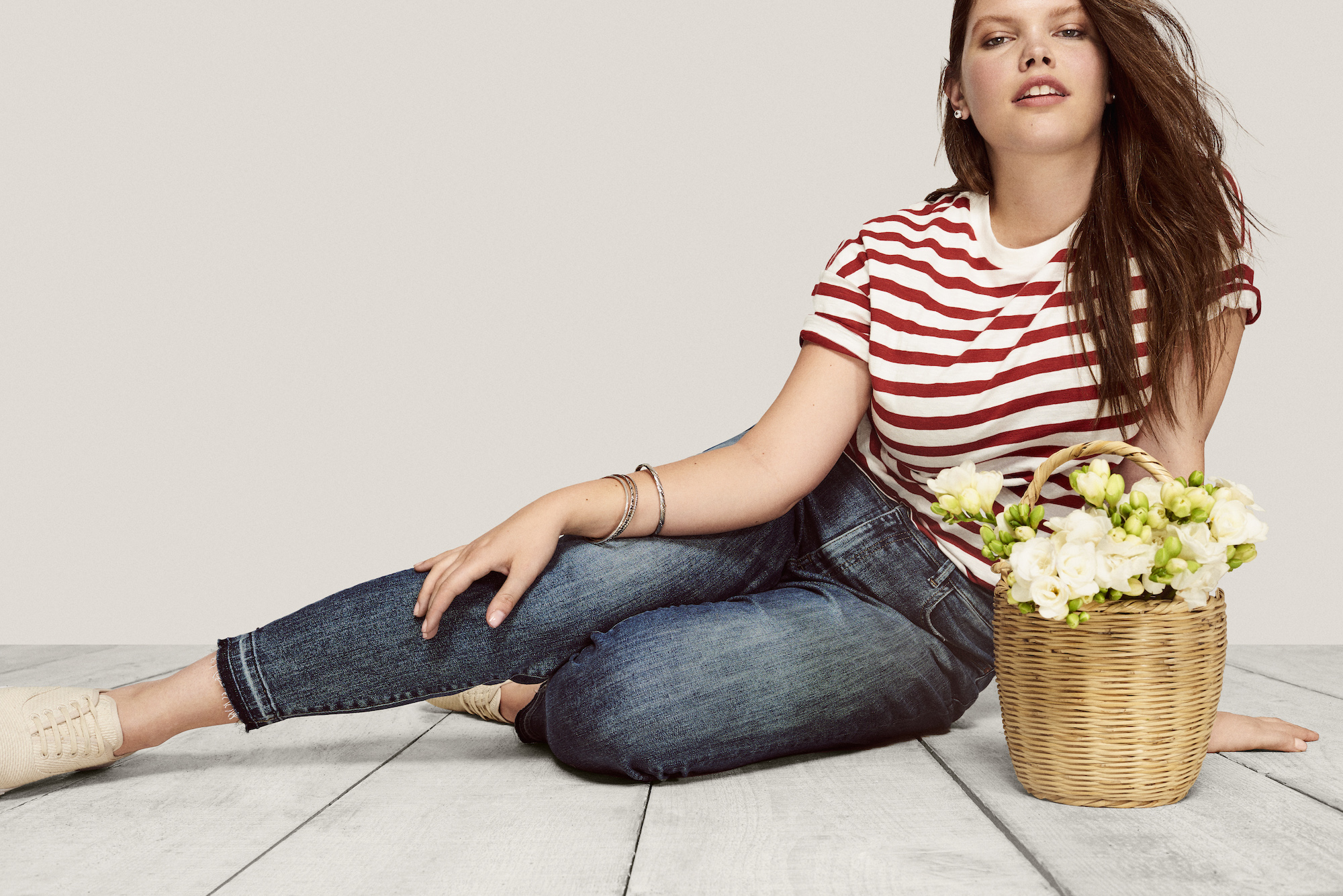 A model wearing blue jeans and a striped shirt