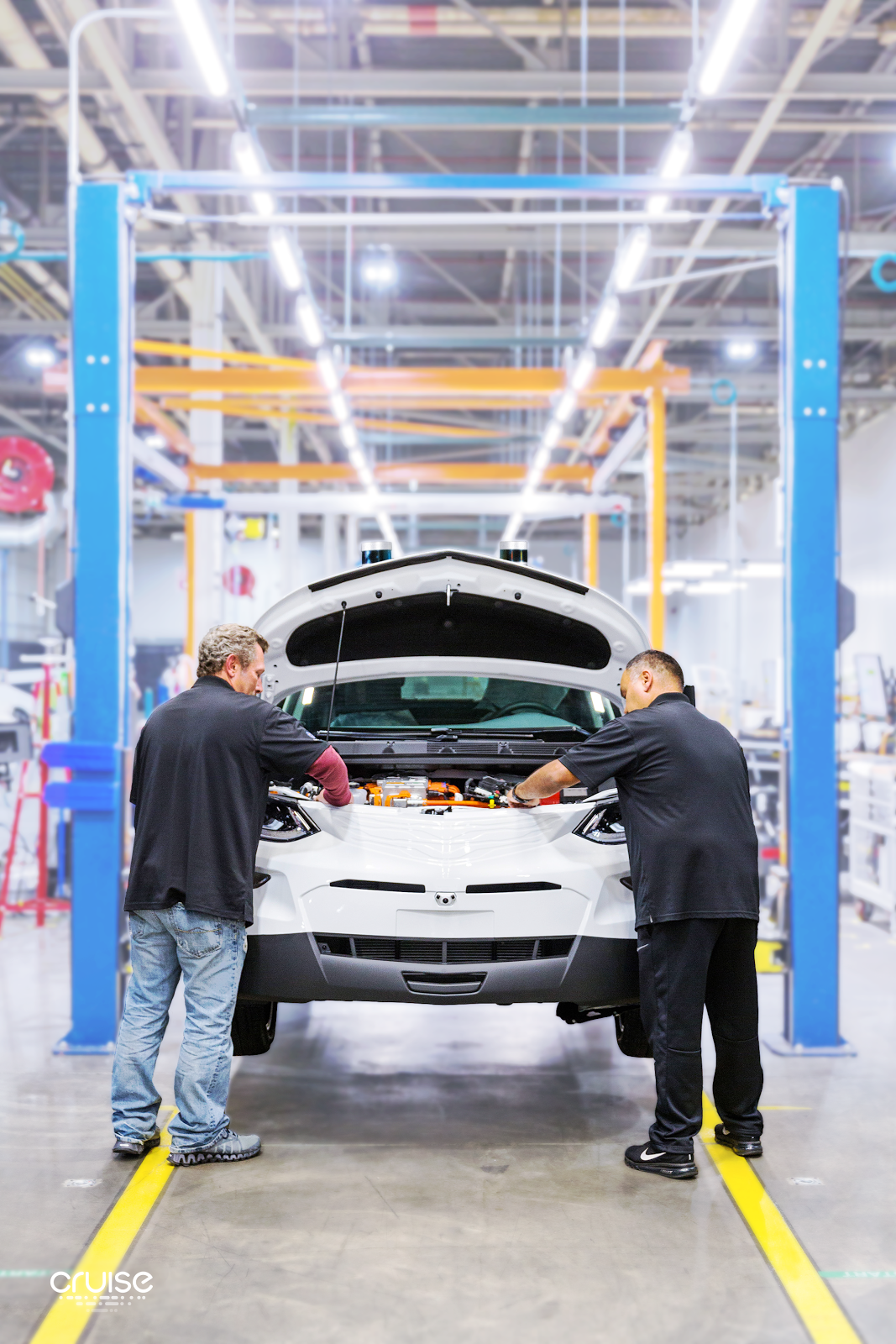 Two workers on an assembly line have their hands inside the engine compartment of a Chevy Bolt electric vehicle.