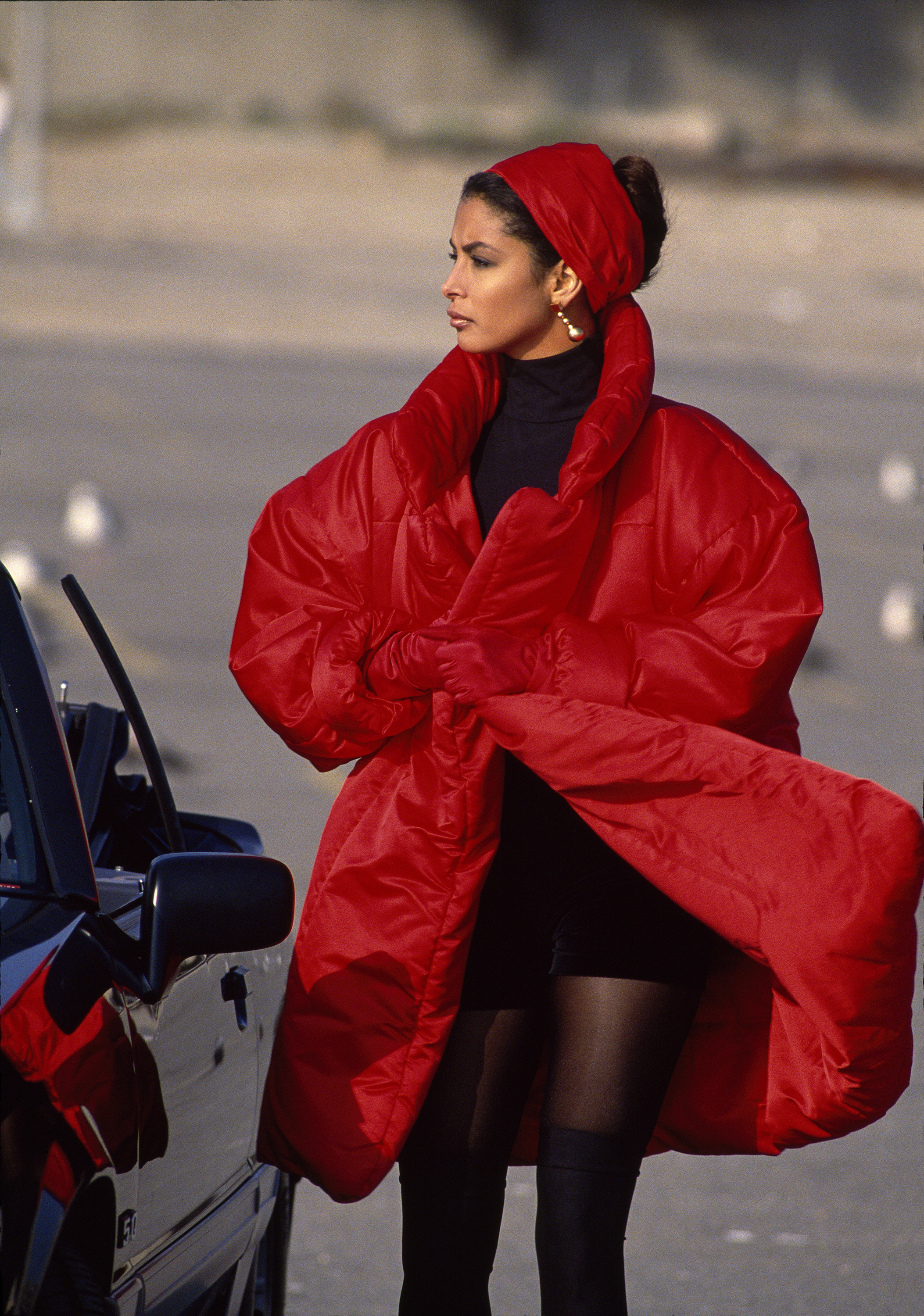 A woman wears a puffy red coat, looking off to the horizon.