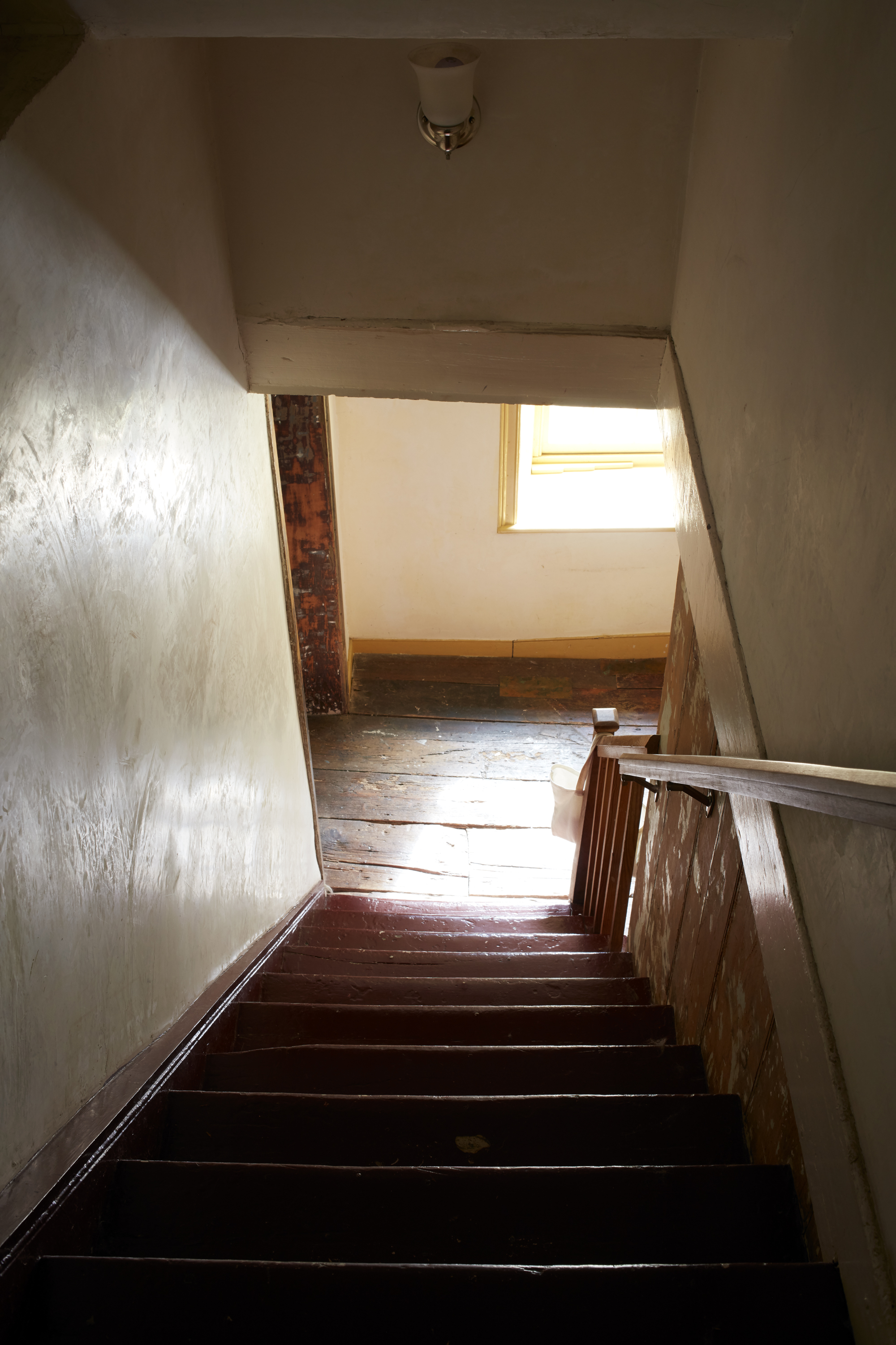 A shot that looks down a wooden stairway surrounded by white plaster walls.
