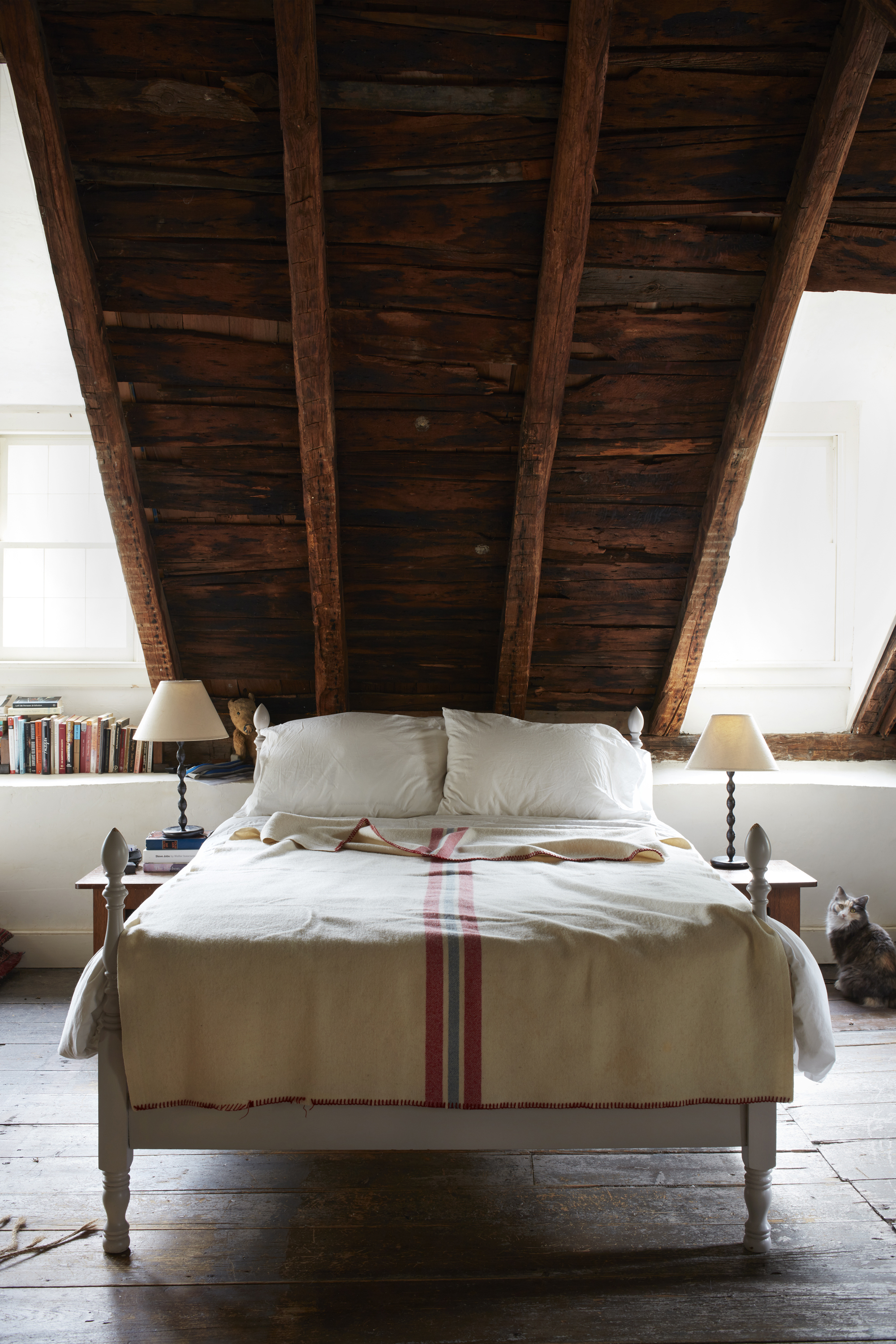A low bed is tucked into an eave beneath a steeply pitched roof.