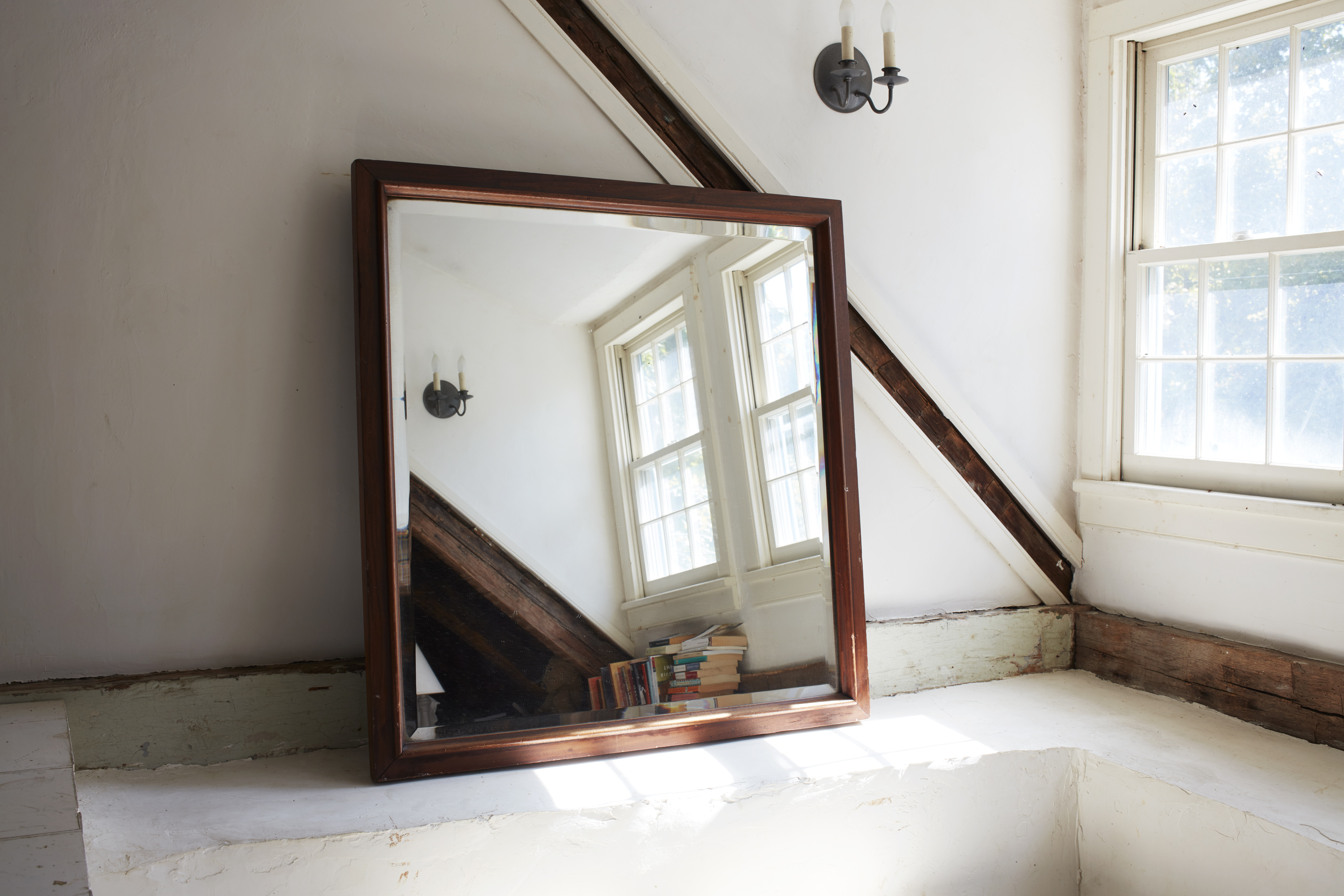 A square mirror stills beside windows and casts light into the room.