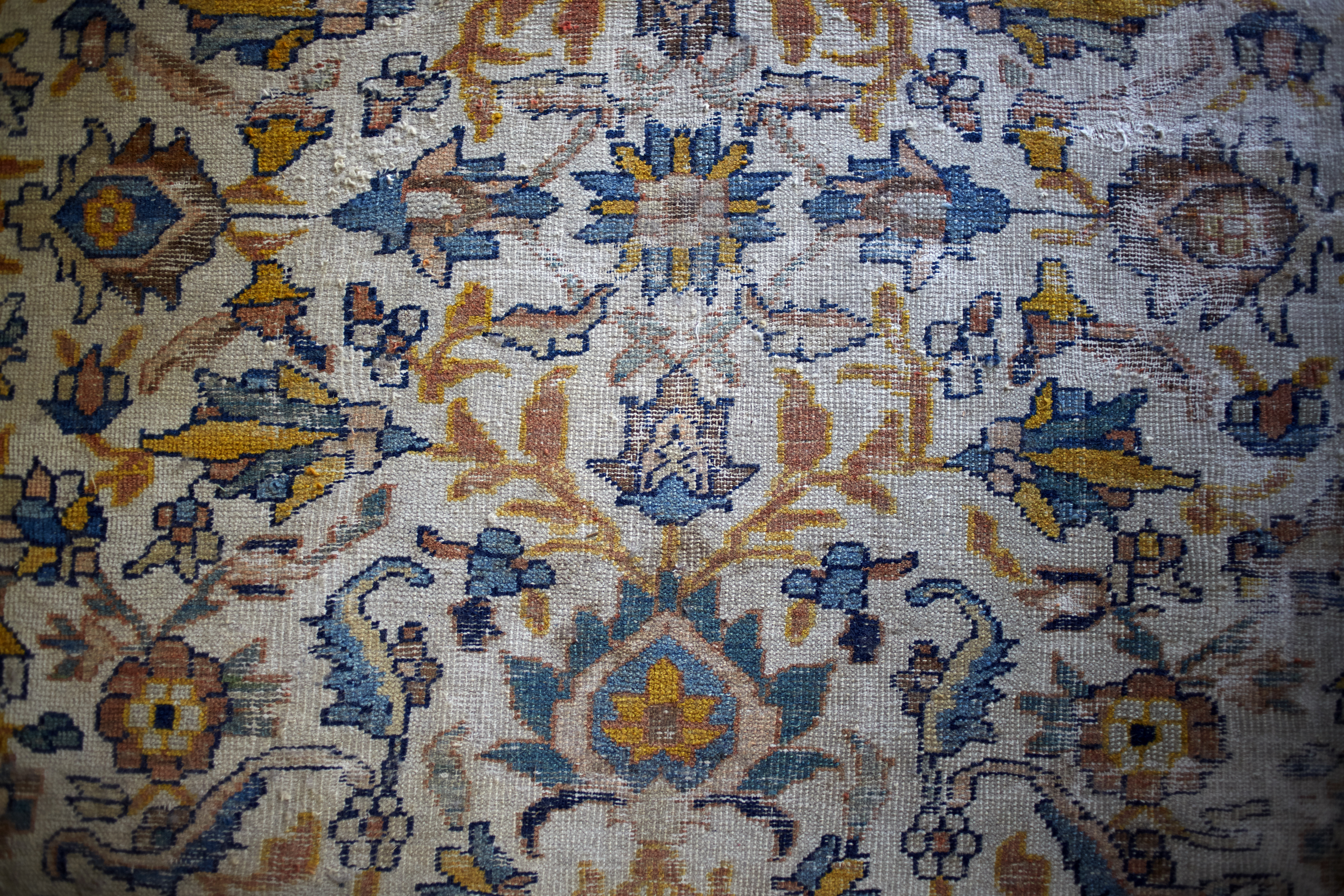 A detail of an antique rug showing a blue-and-gold pattern of flowers and vines.