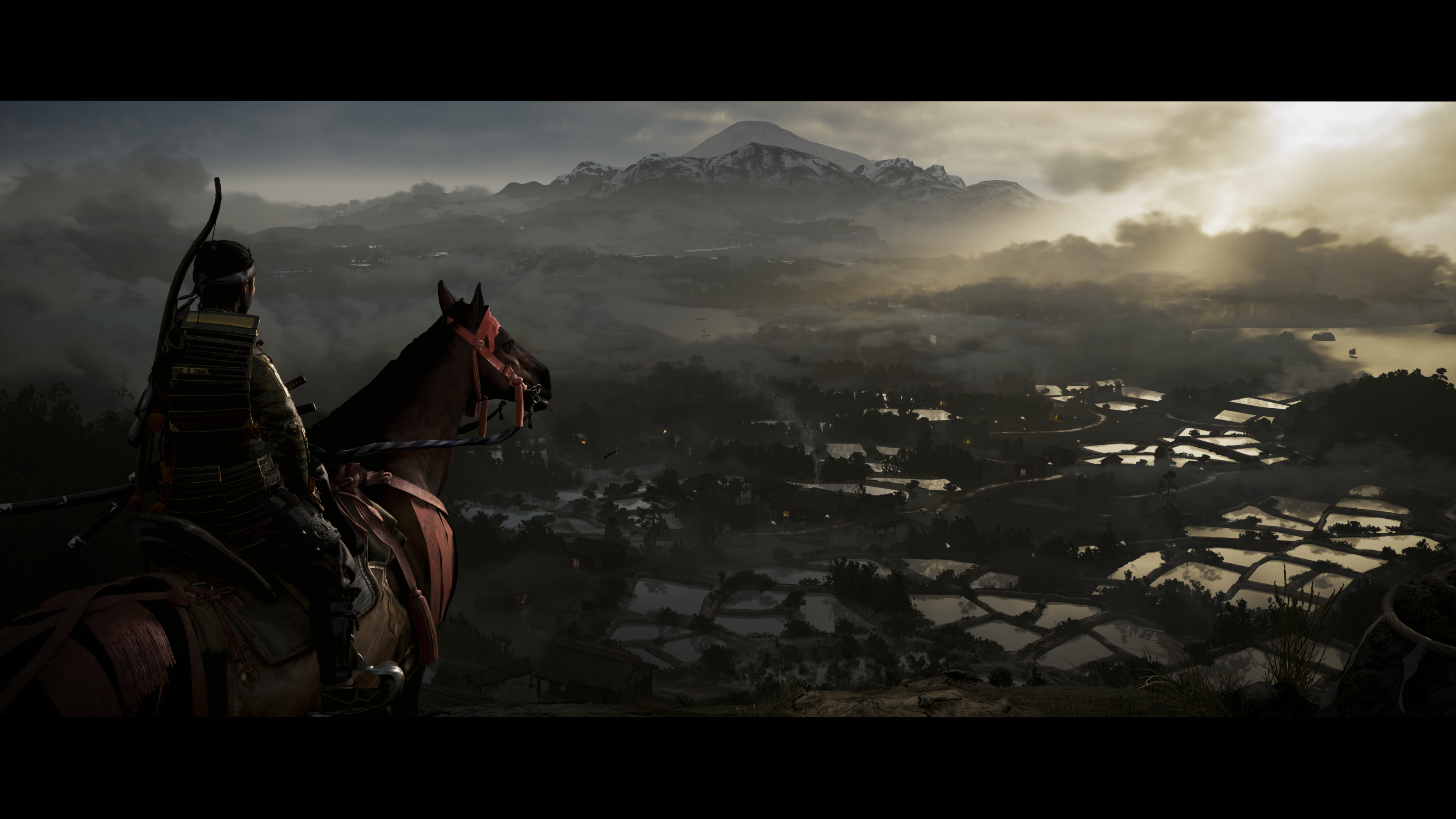 A samurai warrior on horseback stands on a hill overlooking rice pad s Sucker Punch Productions Sony Interactive Entertainment