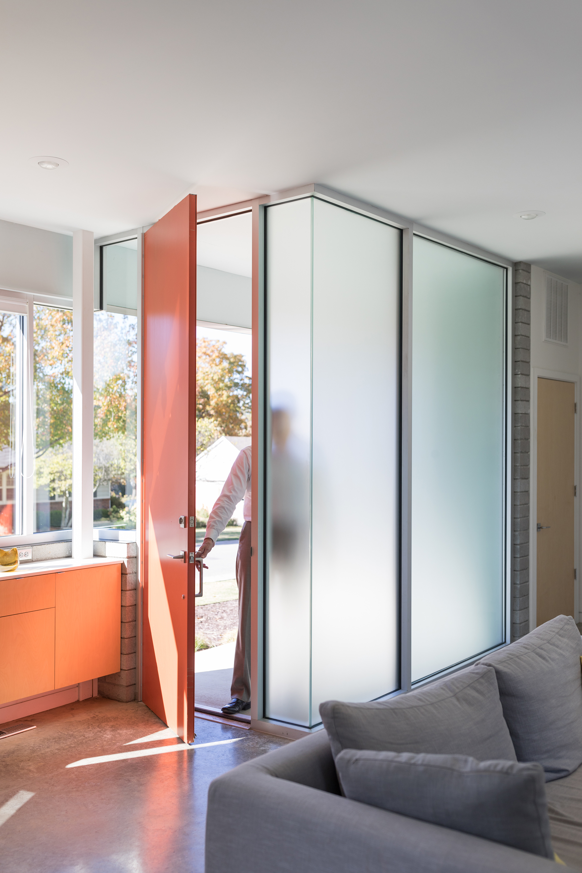 An orange door marks the entry of this modern house with large glass windows and doors.