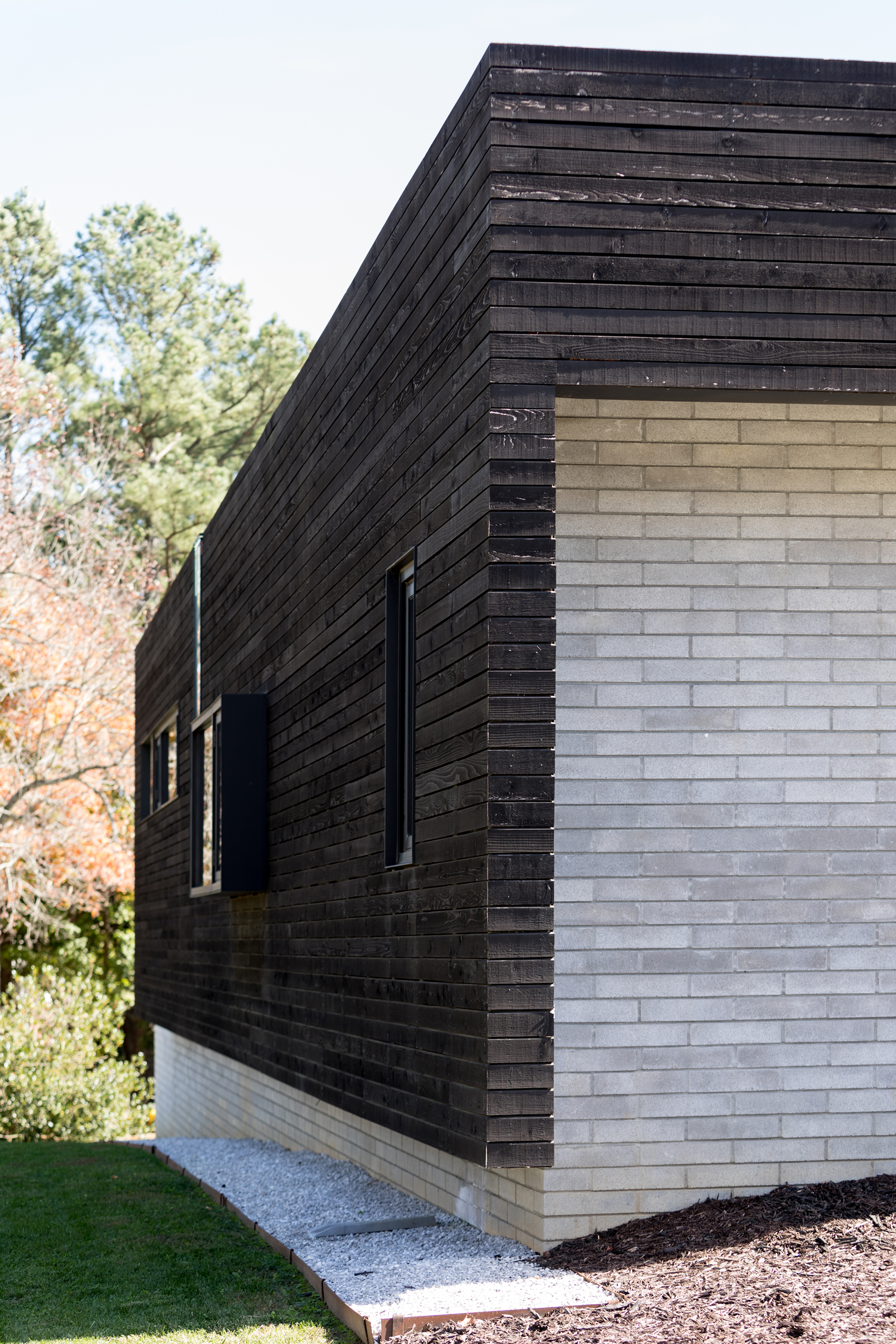 "Shots of the exterior show a wood siding ""shell"" that sits over part of the concrete brick home."
