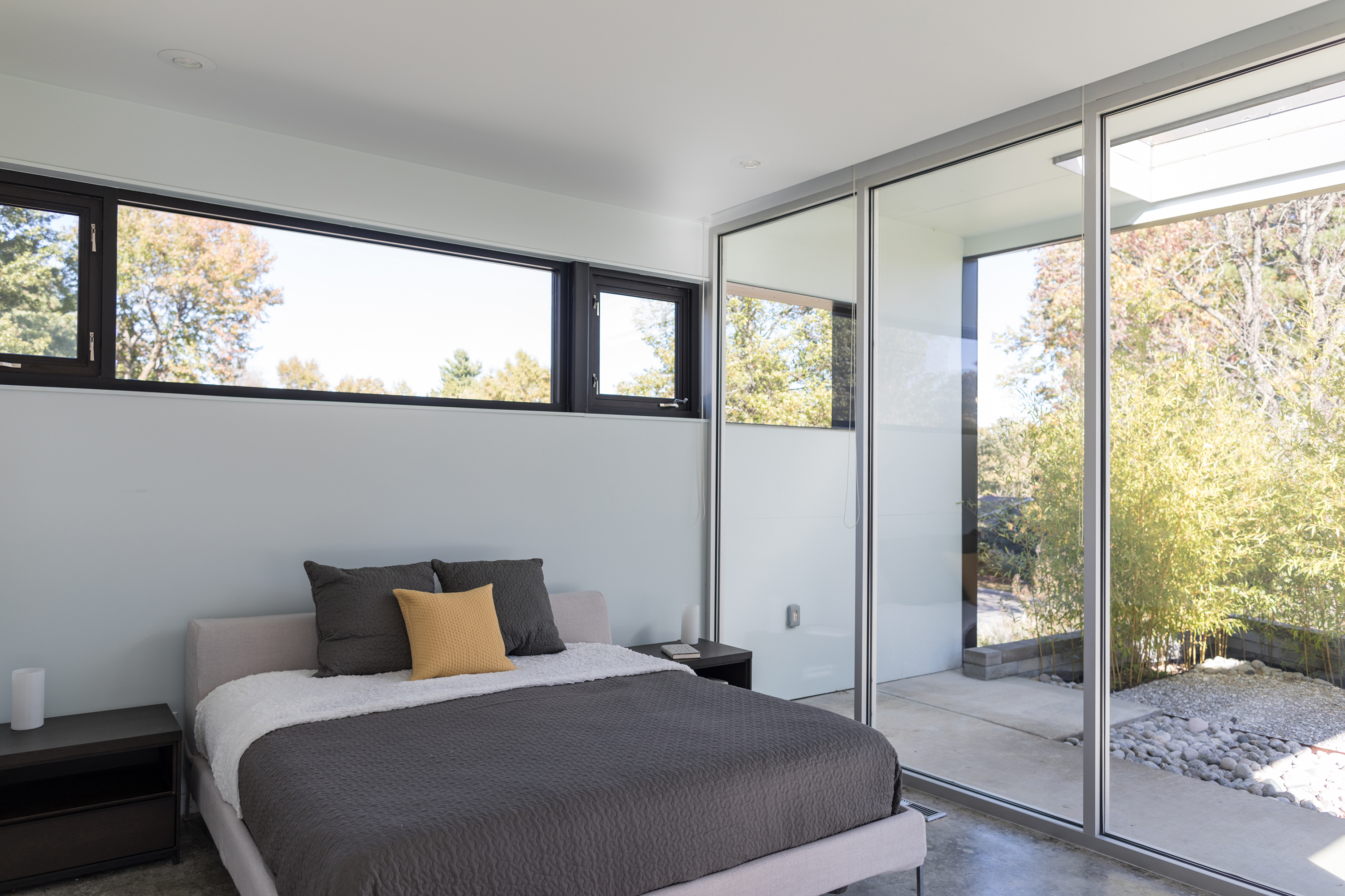 A low, modern tan bed with gray bedding sits beside a wall of glass doors. The yard is visible through the glass.