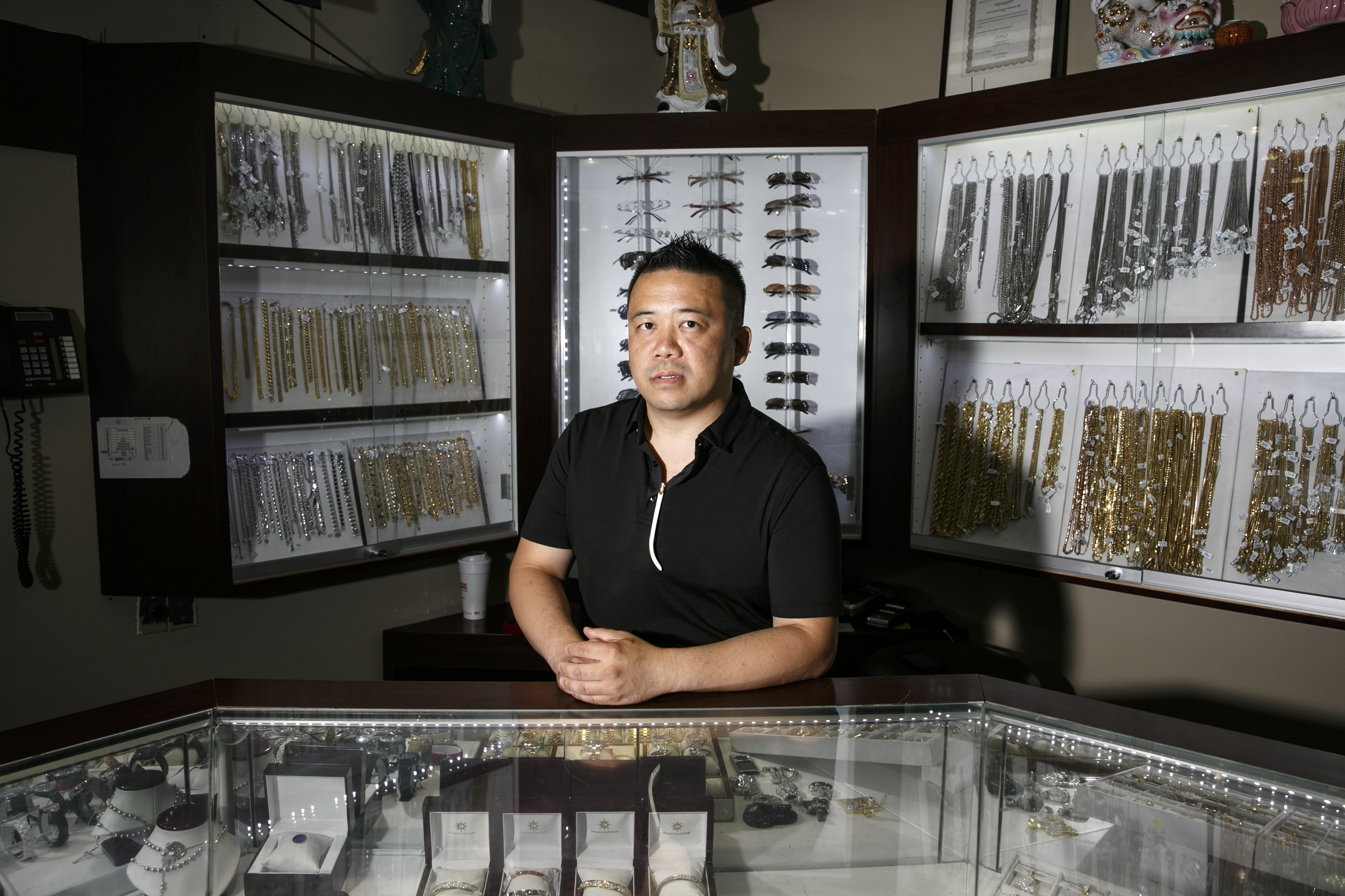 Gary Yee, manager of Golden Sun Jewelry, stands in front of some of the Cartier sunglasses he sells.