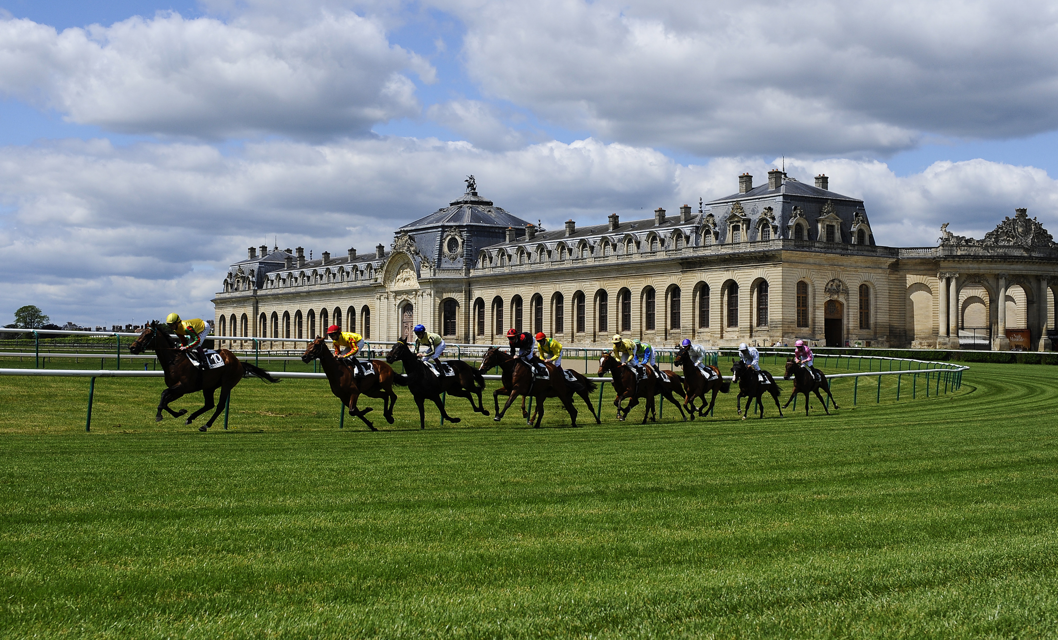 Horses run in front of the Grandes Écuries at majestic Chantilyl Racecourse in France.